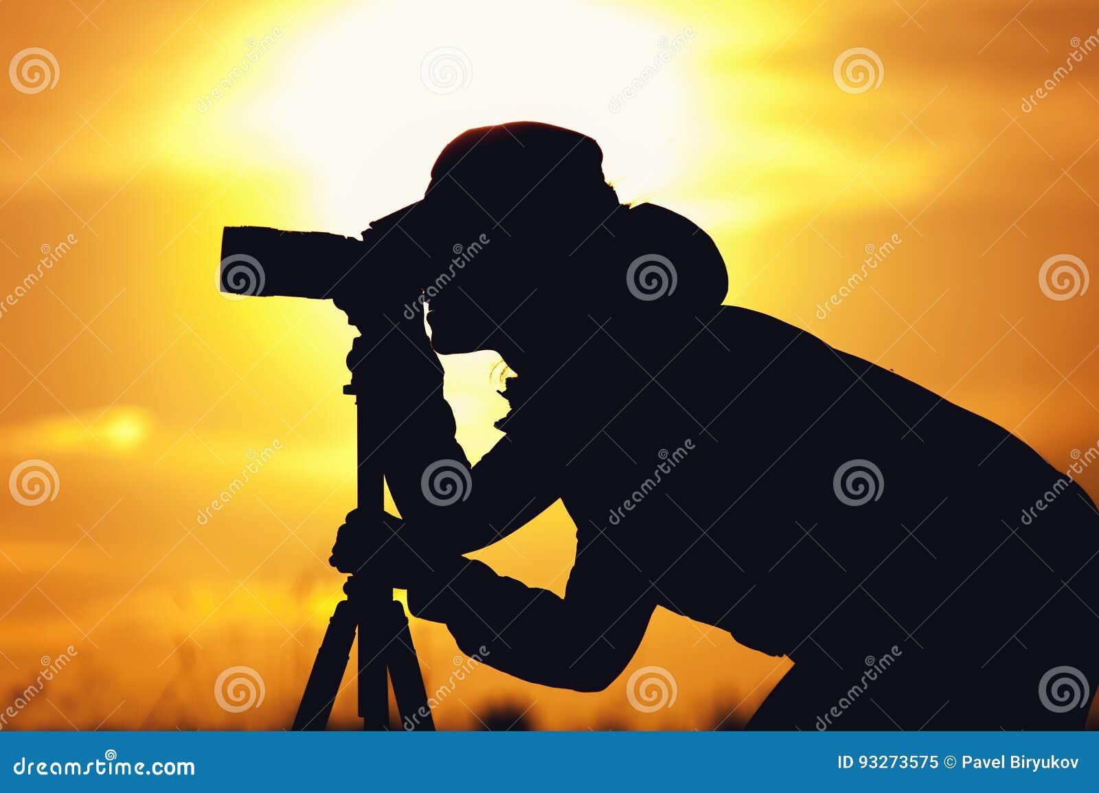 Kontur av den kvinnliga fotografen mot solnedgång