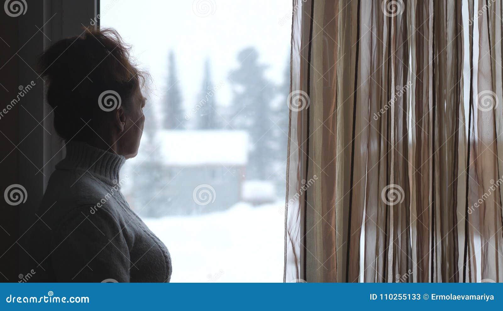 Kontur av den mogna kvinnan i åldrigt hålla ögonen på i fönster på snöig berg