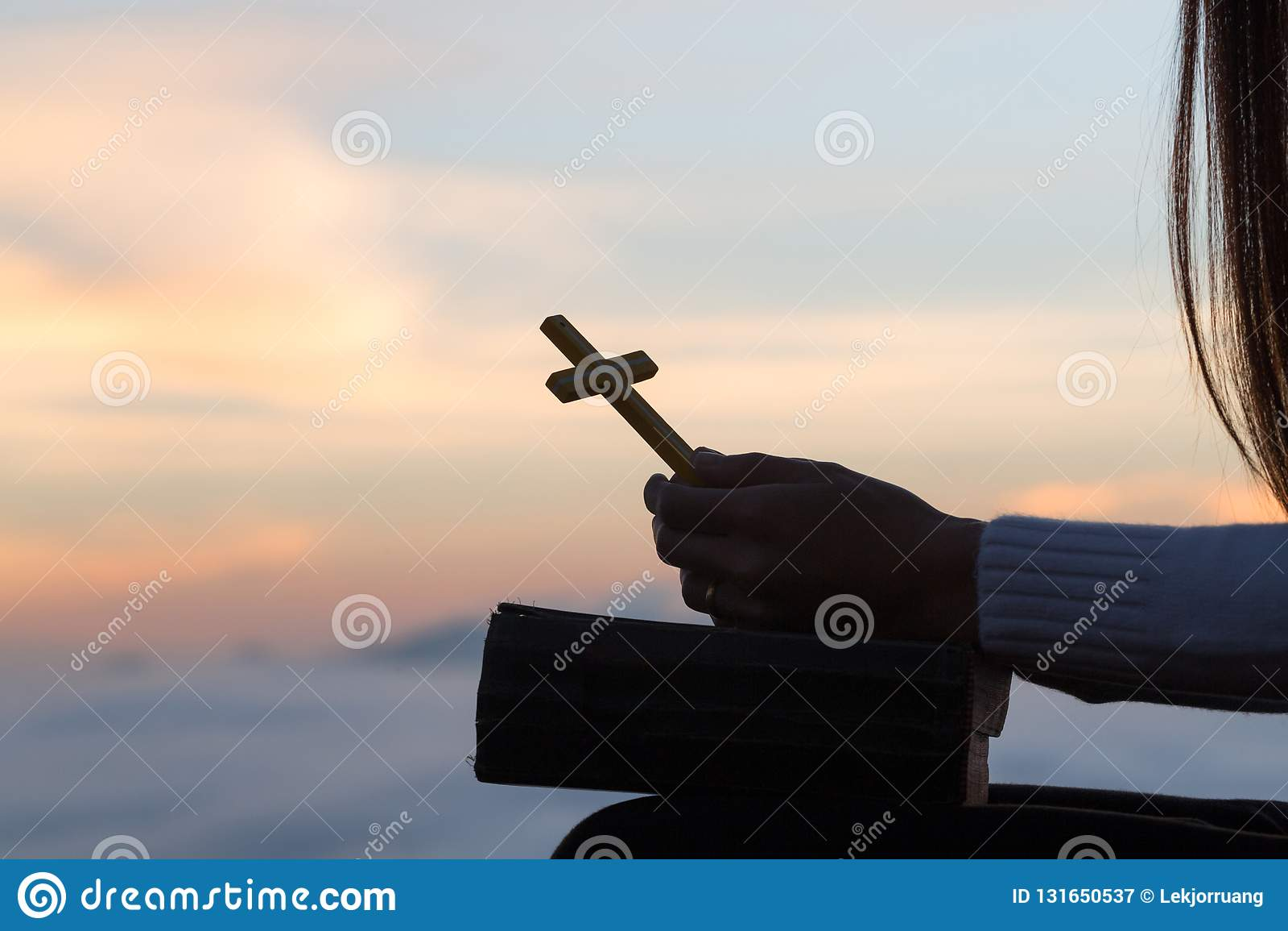 Kontur av den unga kvinnan som ber med kors och biblar på soluppgång, Christian Religion begreppsbakgrund