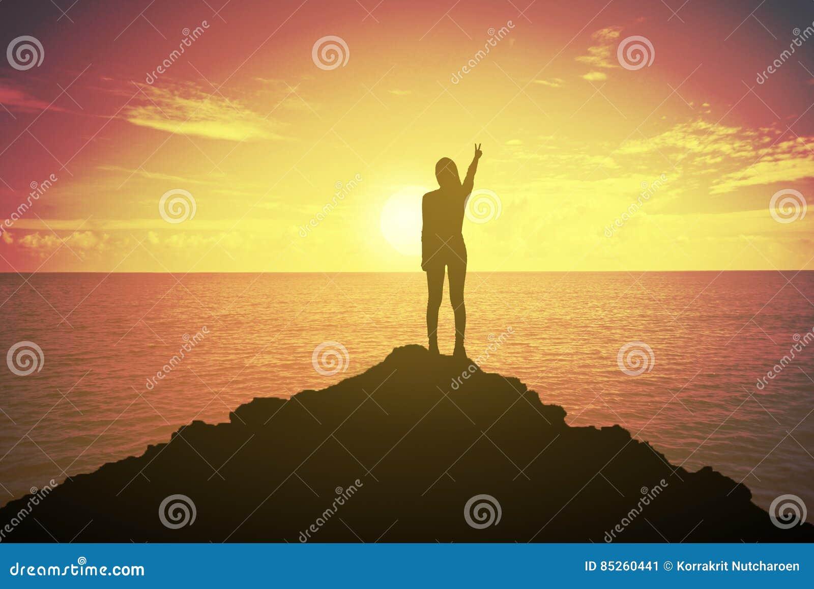 Kontur av den vinnande framgångkvinnan på solnedgången eller soluppgång som upp står och lyfter hennes hand i stridighetbegrepp