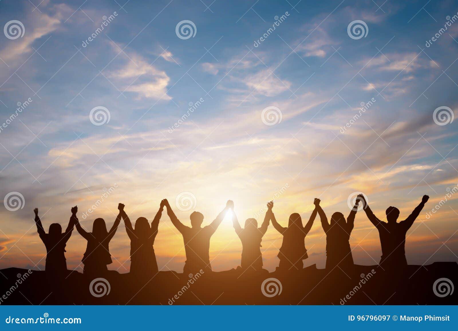 Kontur av det lyckliga affärslaget som gör höjdpunkthänder i solnedgången sk