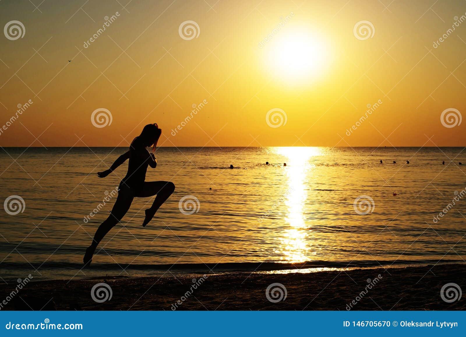 Kontur av en flicka i en baddräkt som kör längs stranden på bakgrunden av gryningen