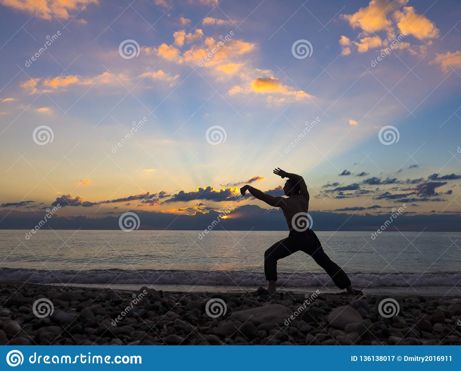 Kontur av en krigs- konstnär som bara utbildar på havspir som öva hans flyttningar på solnedgång Aktivt liv och