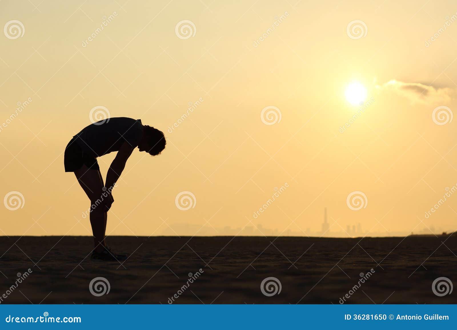 Kontur av en utmattad idrottsman på solnedgången