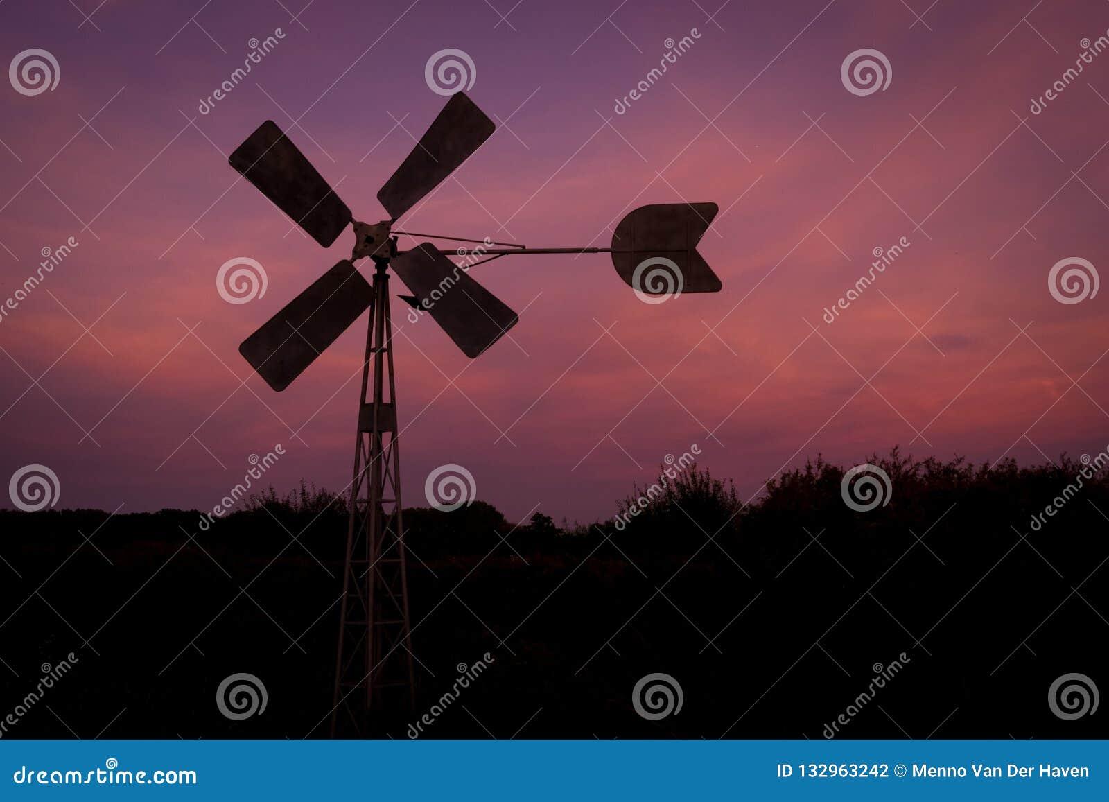 Kontur av en väderkvarn mot en purpurfärgad aftonhimmel nära gouda, Holland