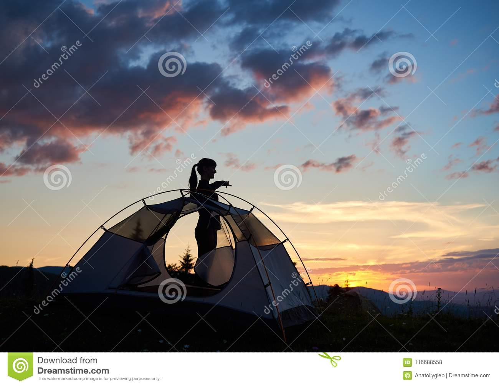 Kontur av ett attraktivt flickaanseende i profil nära tältet under morgonhimlen på gryningen