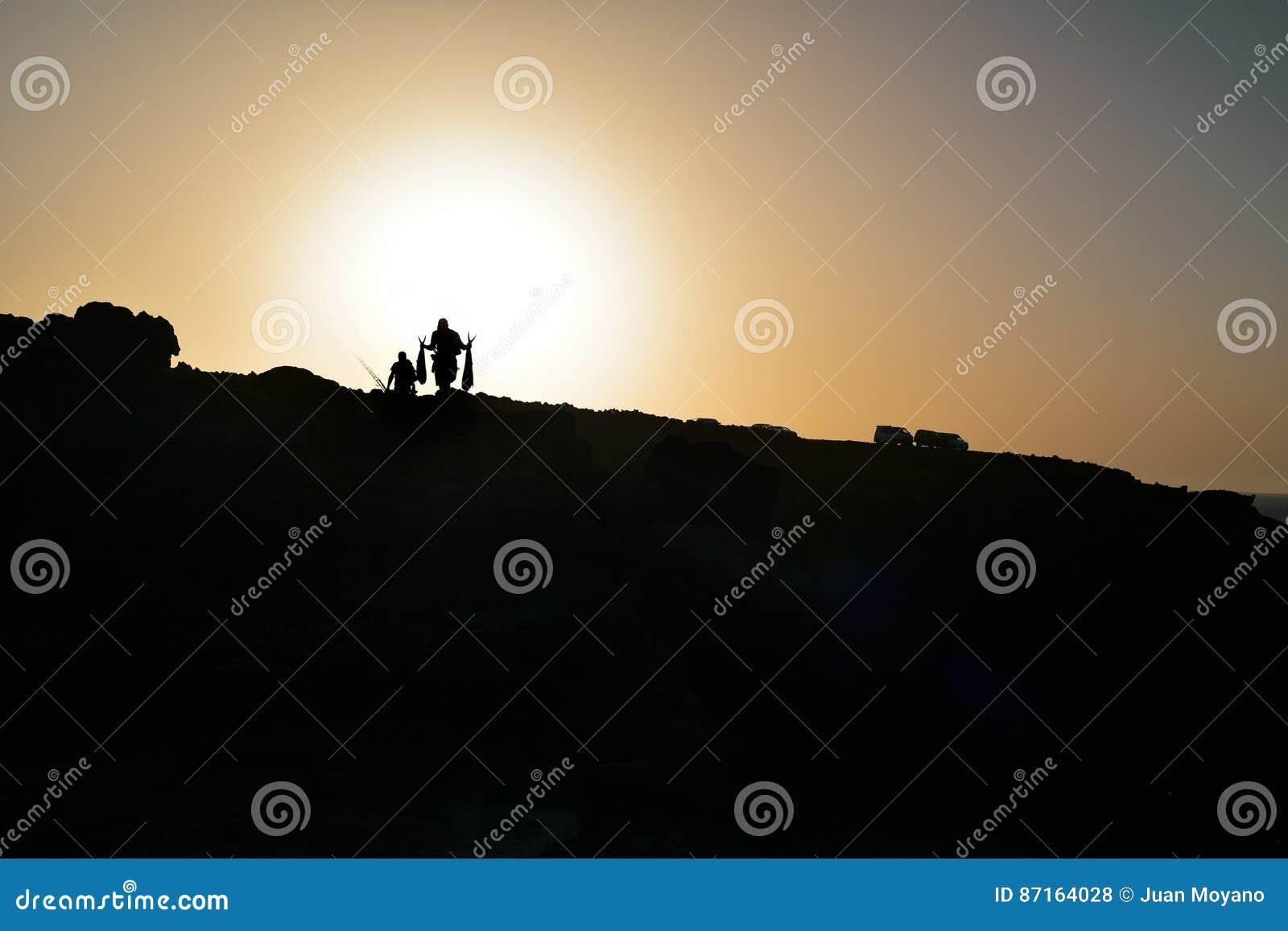 Kontur av fiskare på en klippa på skymning