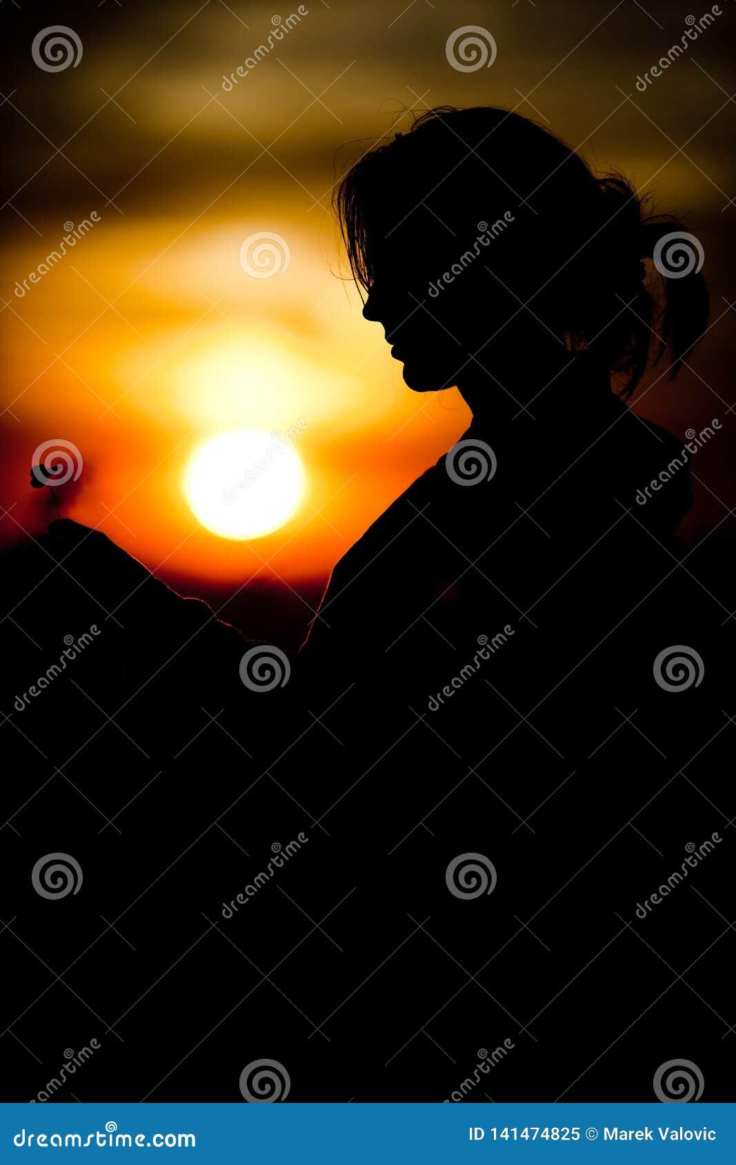 Kontur av flickas klöverbladskorsningen för framsidainnehav under svarta och orange färger för solnedgång -