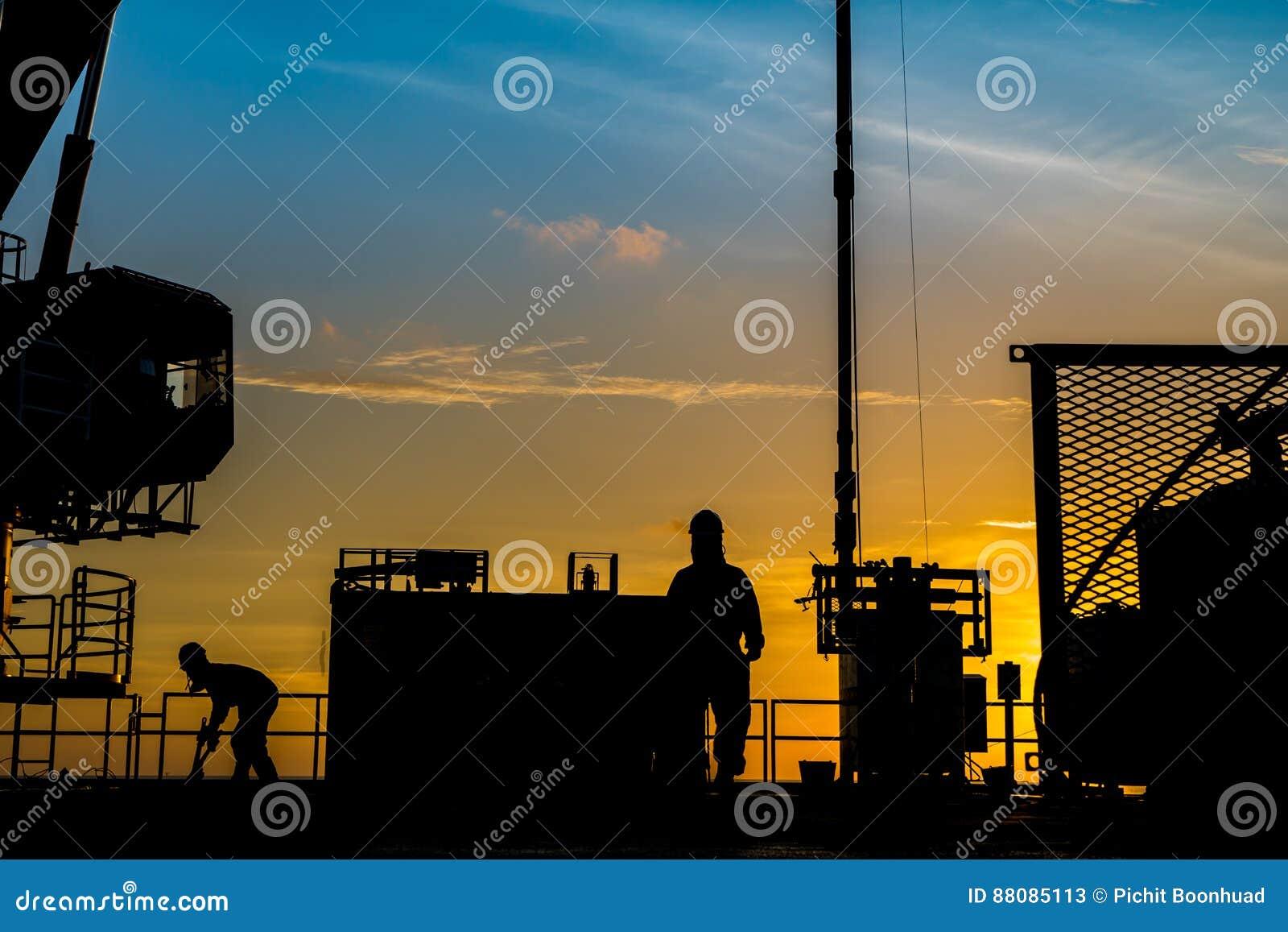 Kontur av fossila bränslenwellheadplattformen och den tjänste- arbetaren för brunn, medan arbeta till behållaren för gas för perf