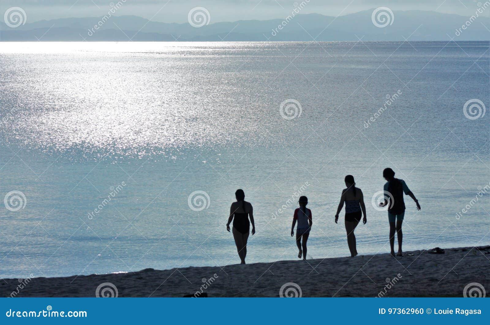 Kontur av fyra damer under solnedgång