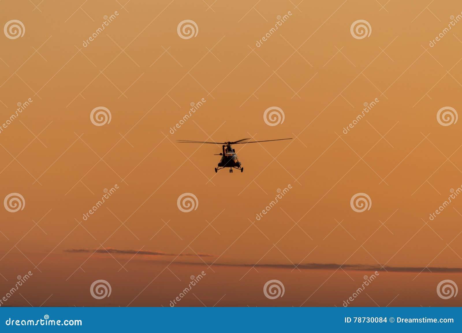Kontur av helikoptern med solnedgånghimmel