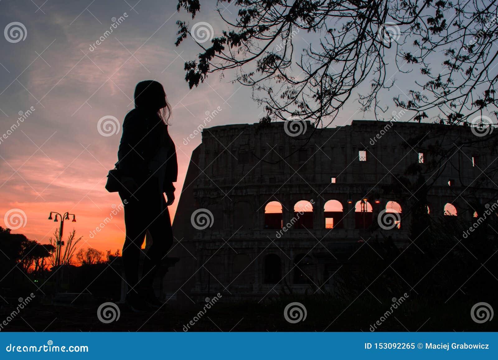Kontur av kvinnan mot färgrik solnedgånghimmel och Colosseum i Rome Italien