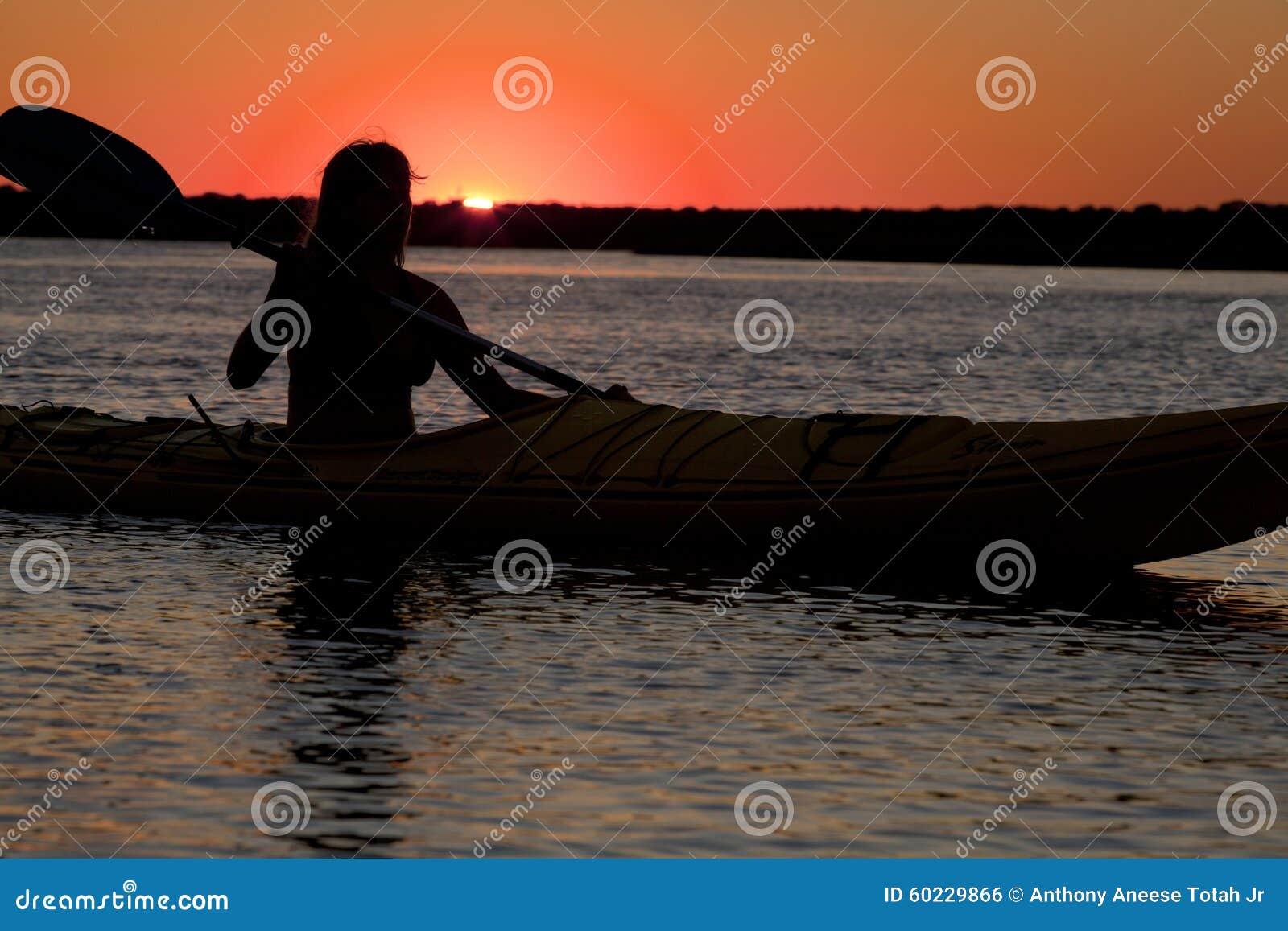 Kontur av kvinnan som kayaking