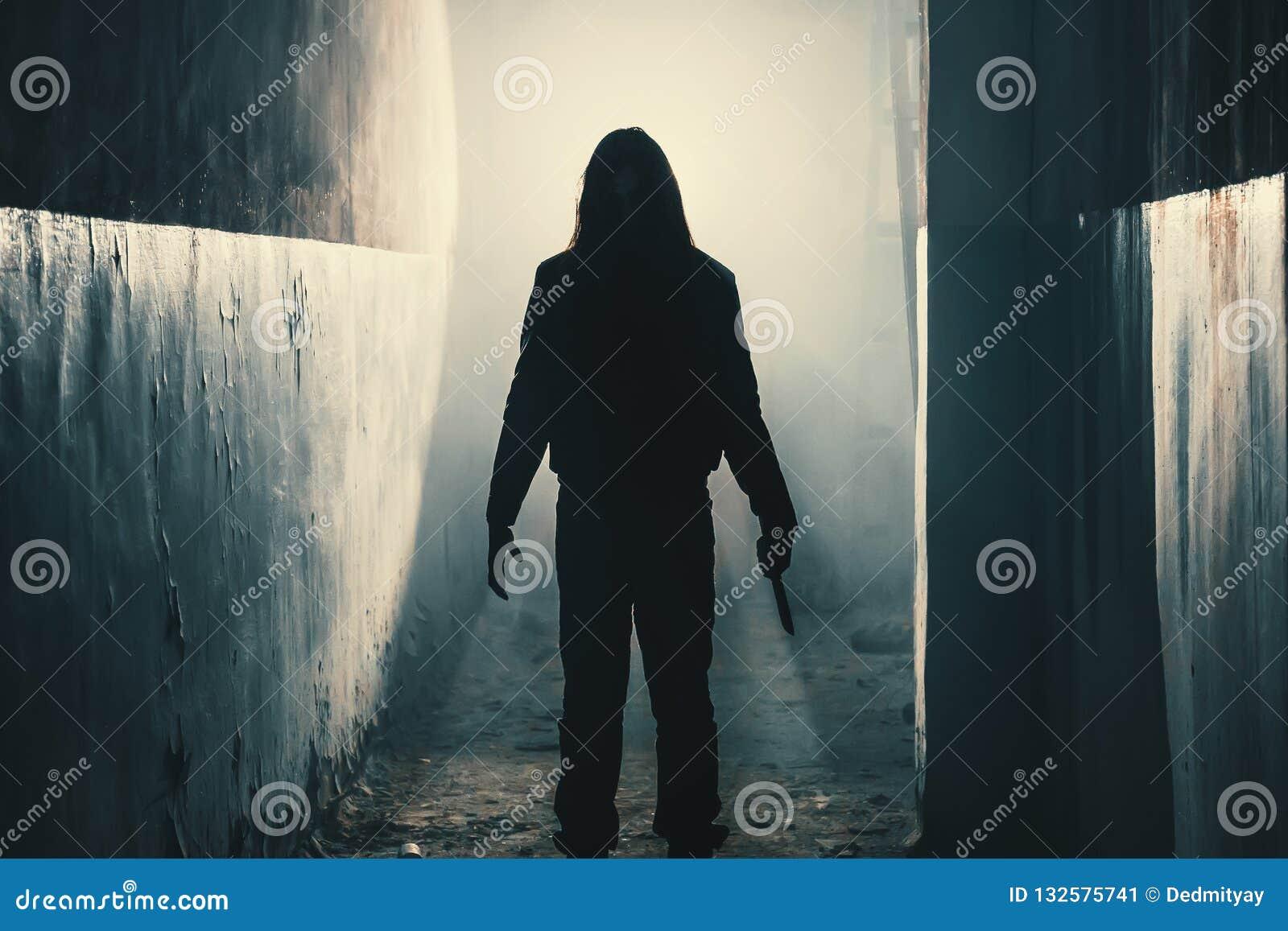 Kontur av mangalningen eller mördaren eller fasamördaren med kniven i hand i mörk kuslig och spöklik korridor Brottslig rånare