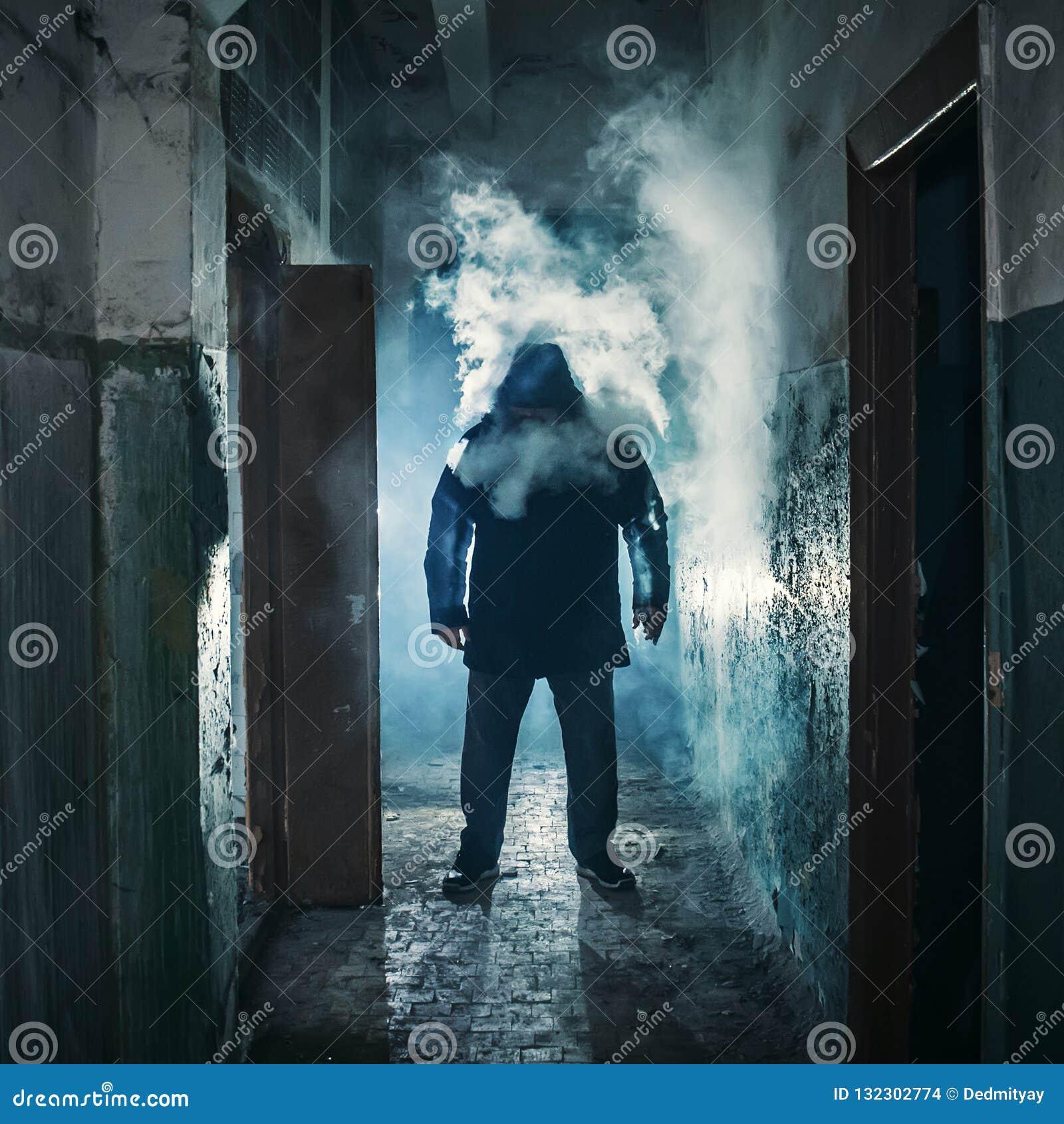 Kontur av mannen i mörk kuslig korridor i moln av vapeånga- eller dunströk, gåtafasaatmosfär