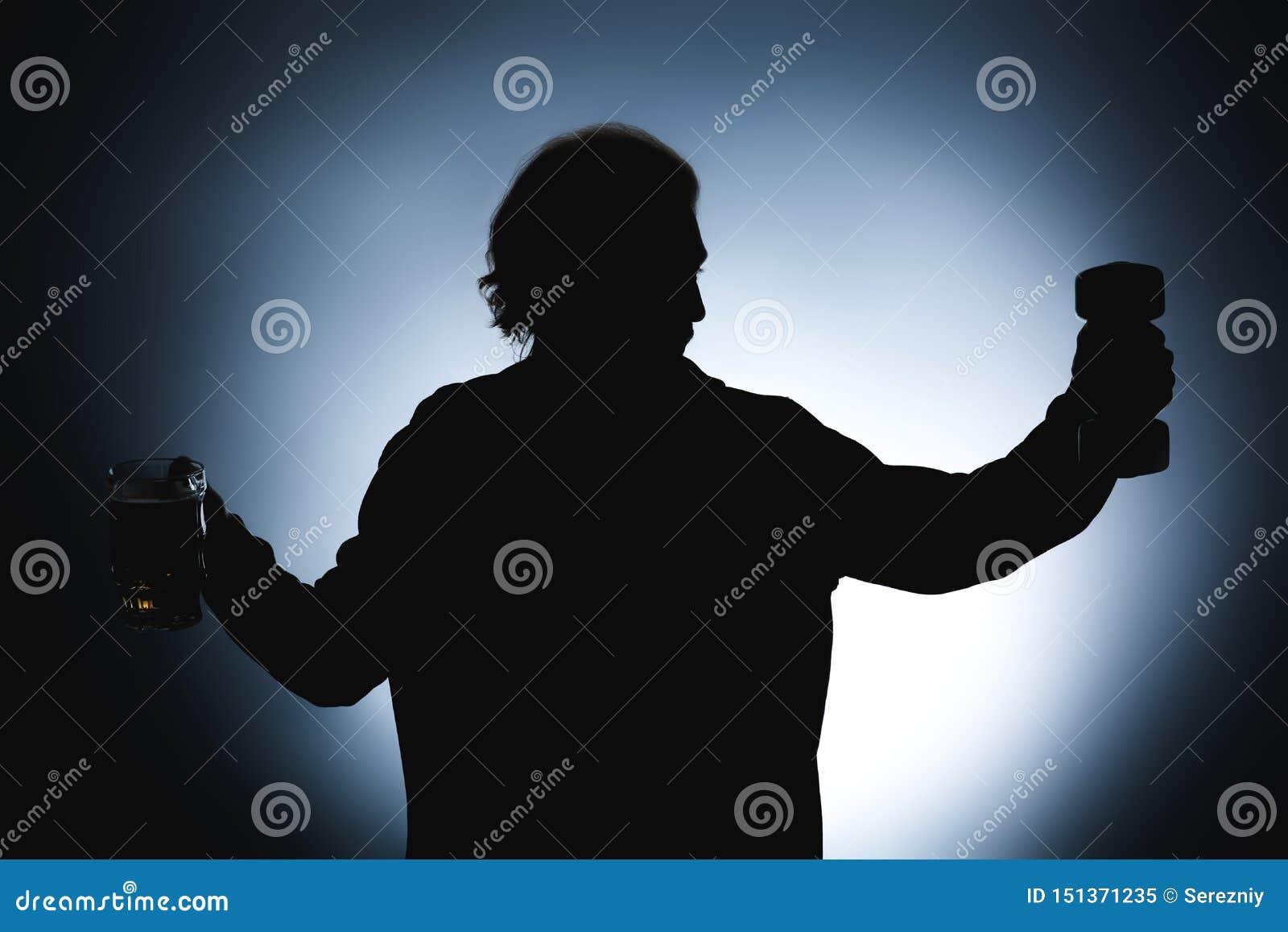 Kontur av mannen med hanteln och att råna av öl på mörk bakgrund Begrepp av valet mellan alkohol och sporten
