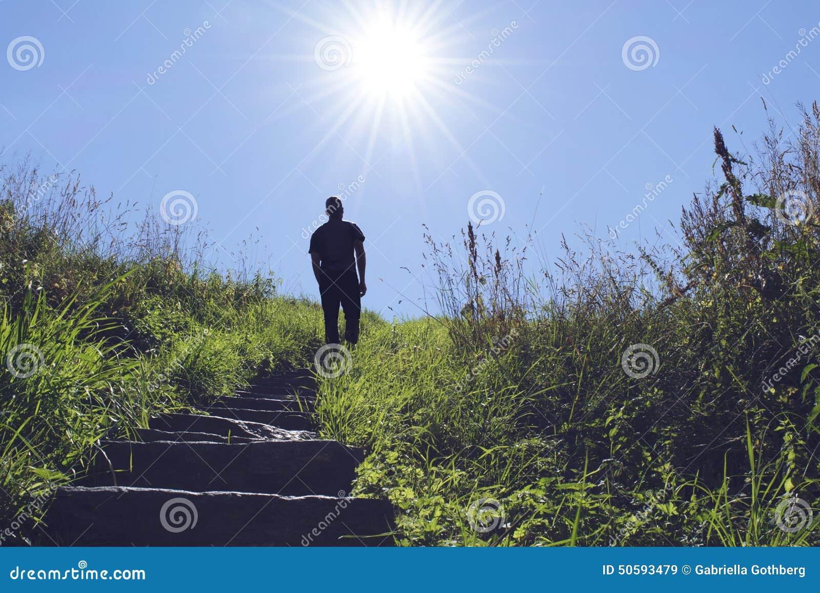 Kontur av mannen som går upp en trappa in mot solen