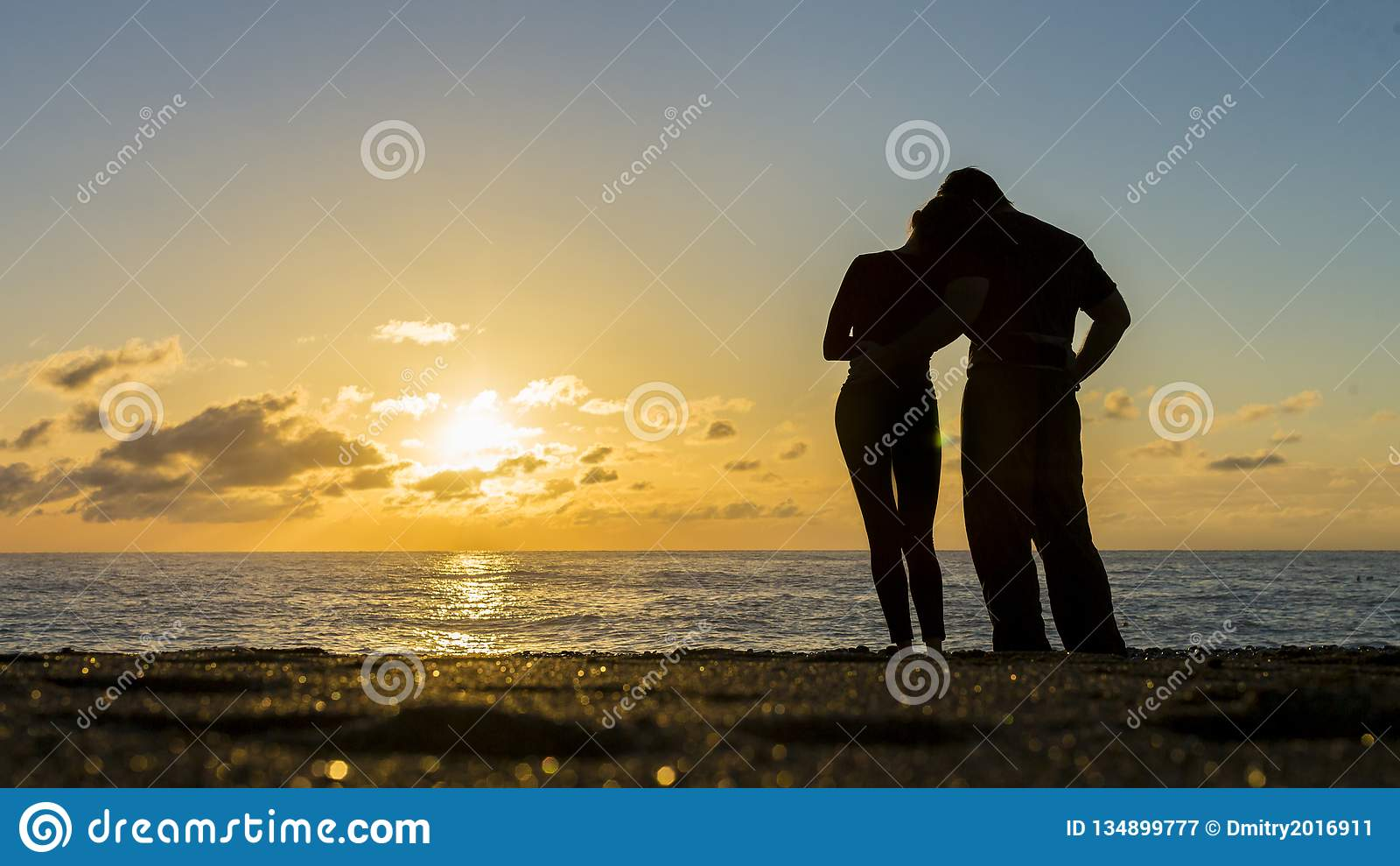 Kontur av par på stranden med en härlig solnedgång i bakgrund