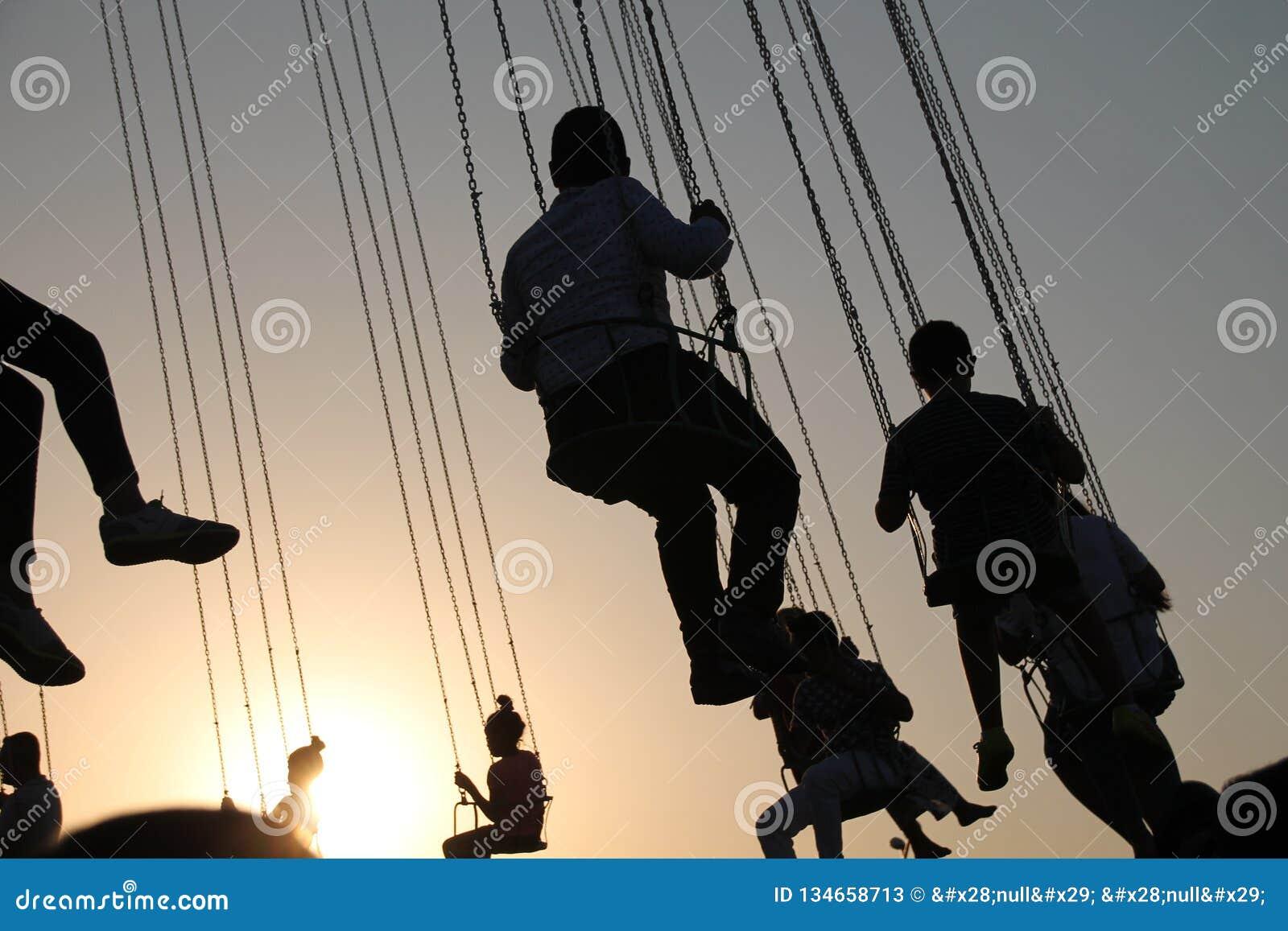 Kontur av ungdomarpå pariserhjulen och svängakarusellen i stopprörelse på solnedgångbakgrund
