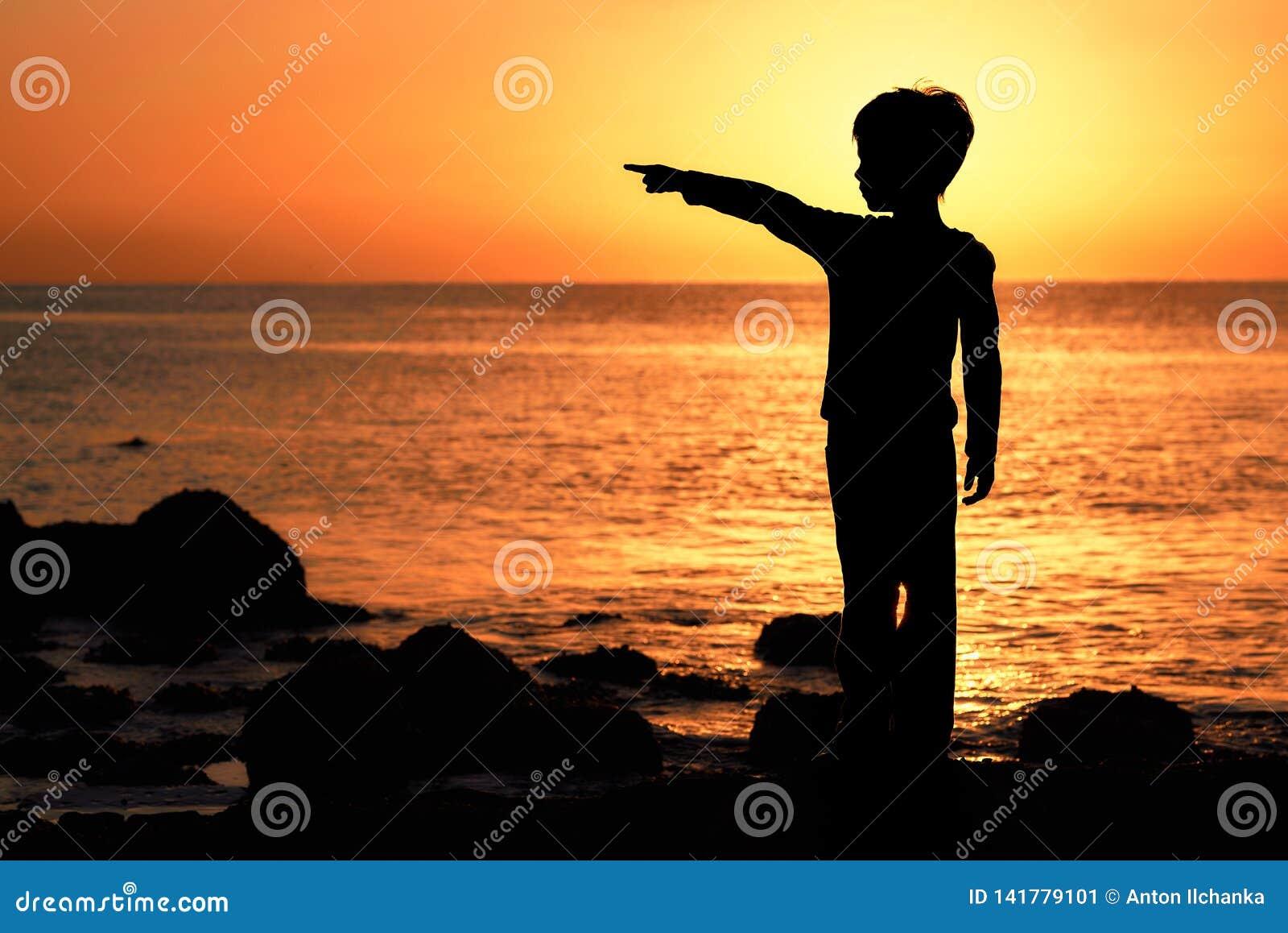 Kontur eines Jungen mit den Daumen angehoben bei Sonnenaufgangsonnenuntergang auf der Küste