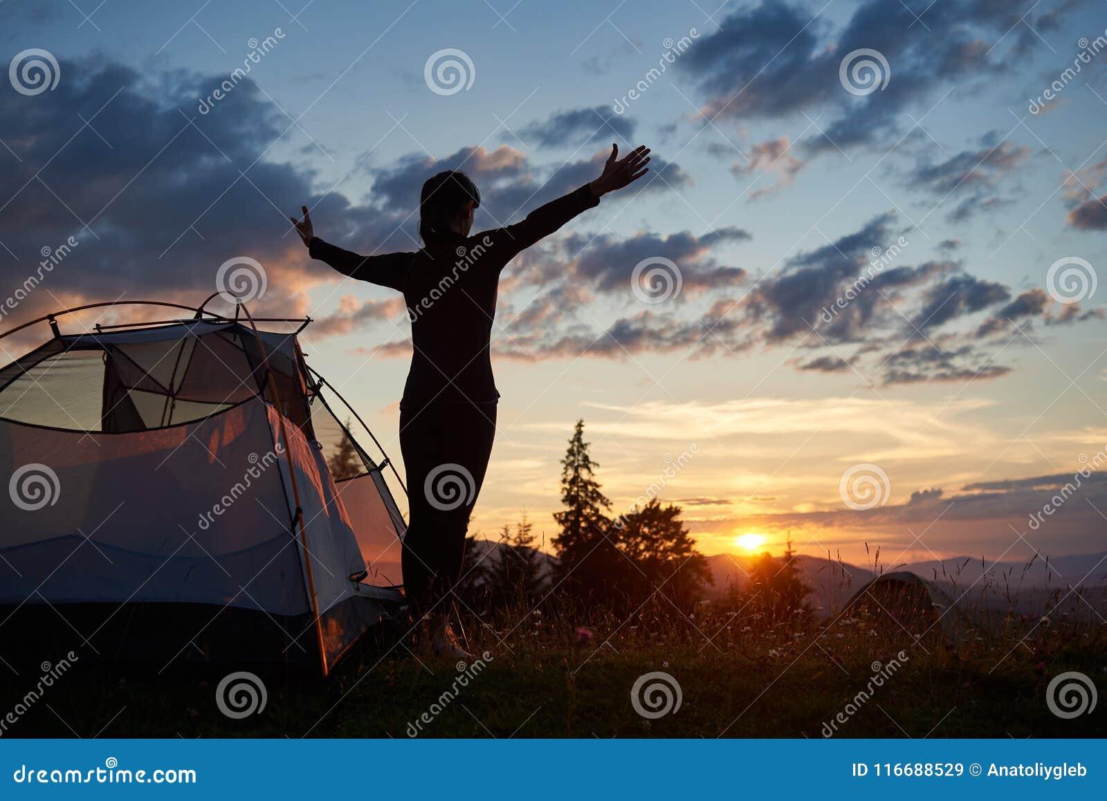 Kontur för bakre sikt av det kvinnliga anseendet med near campa för öppna armar i berg på soluppgång