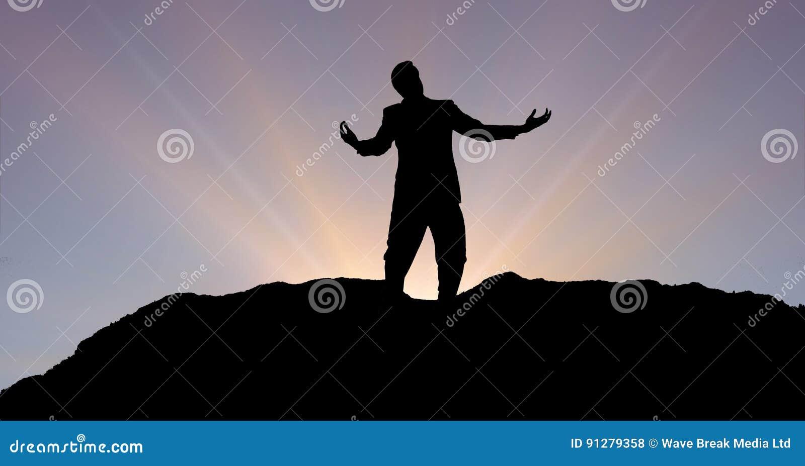 Konturaffärsman med armar som är utsträckta på berget under solnedgång