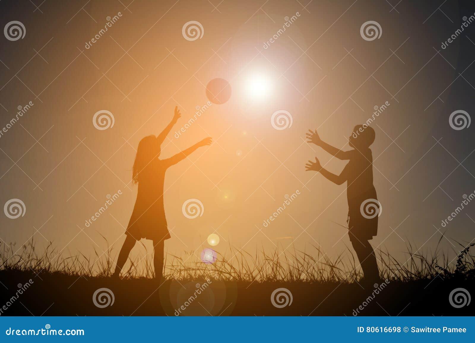 Konturbarn som spelar fotboll på himmelsolnedgången Tid på