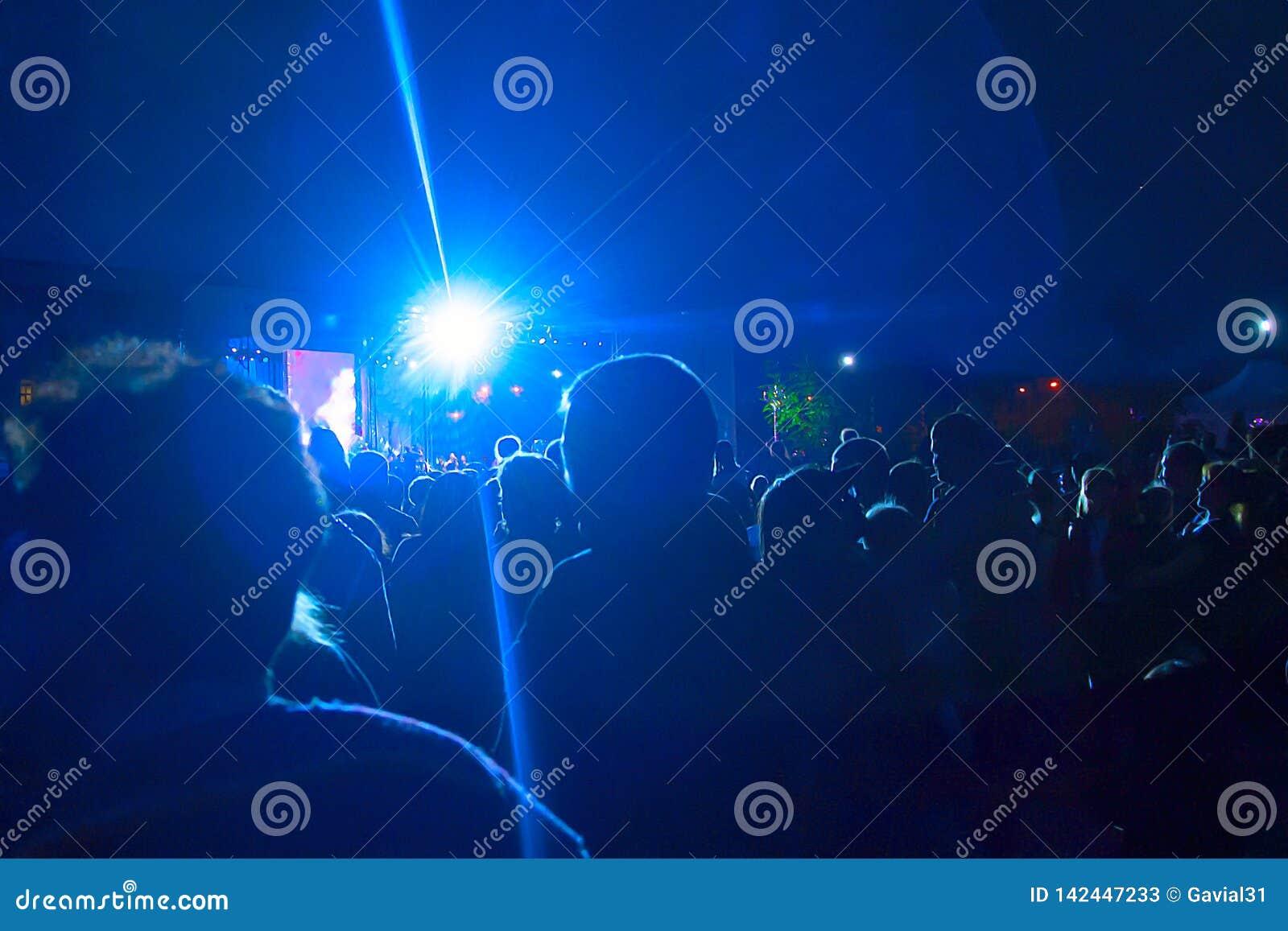 Konturer av ett stort antal folk på bakgrunden av strålkastare Begrepp: beröm samlar