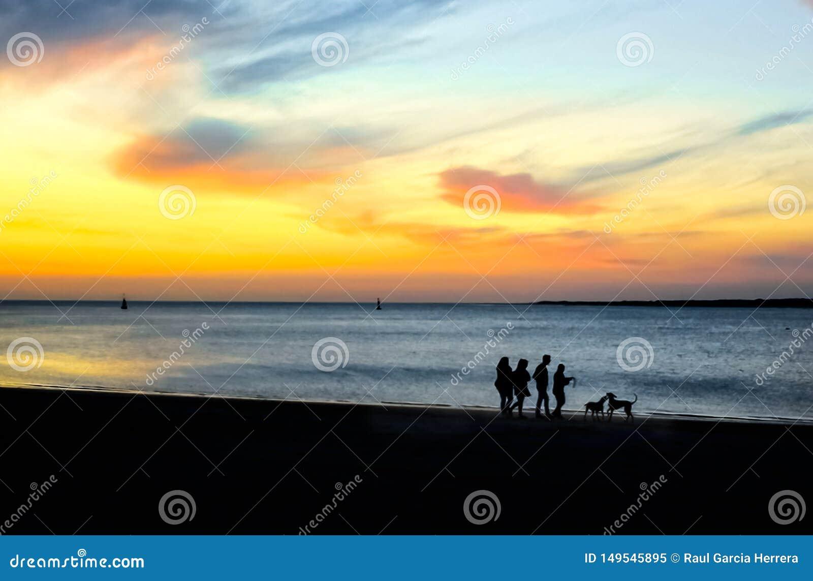 Konturer av folk som går på stranden på solnedgången Episk dramatisk solnedg?ng
