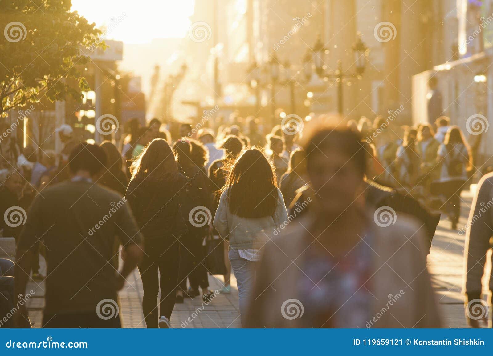 Konturer av folk tränger ihop att gå ner gatan på sommaraftonen, härligt ljus på solnedgången