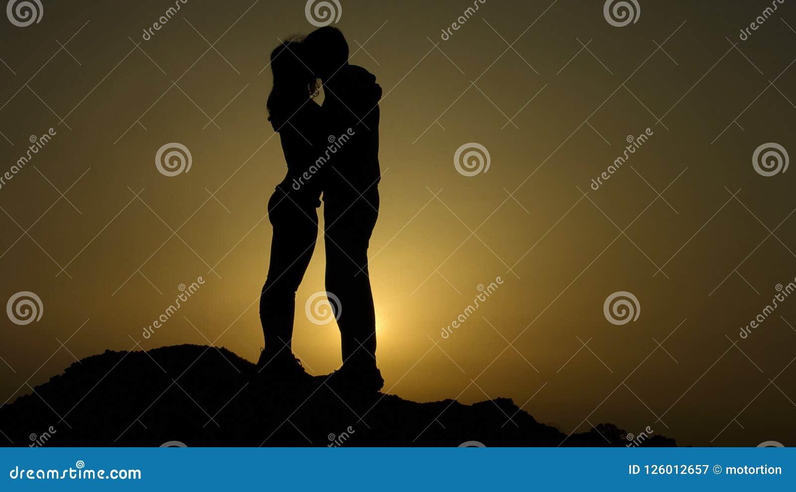 Konturer av nygifta personer kopplar ihop att kyssa passionately, den romantiska kärlekshistorien