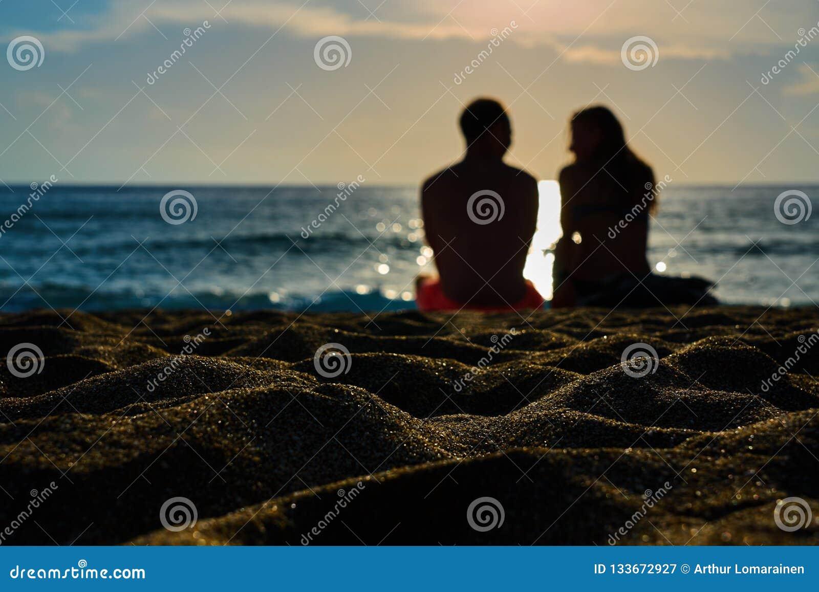 Konturer av par, en man och en kvinna sitter på en sandig strand och ser solnedgången på havet på en semester