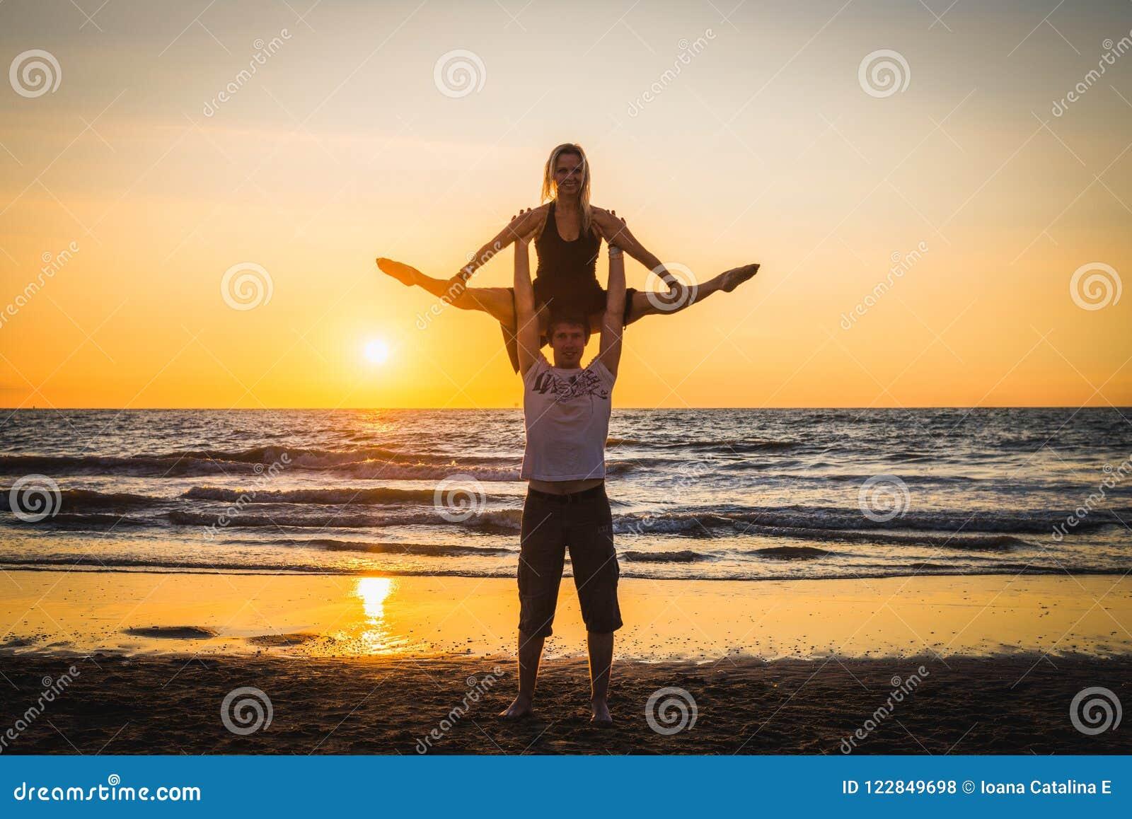Konturer av två dansare som gör akrobatik på solnedgången