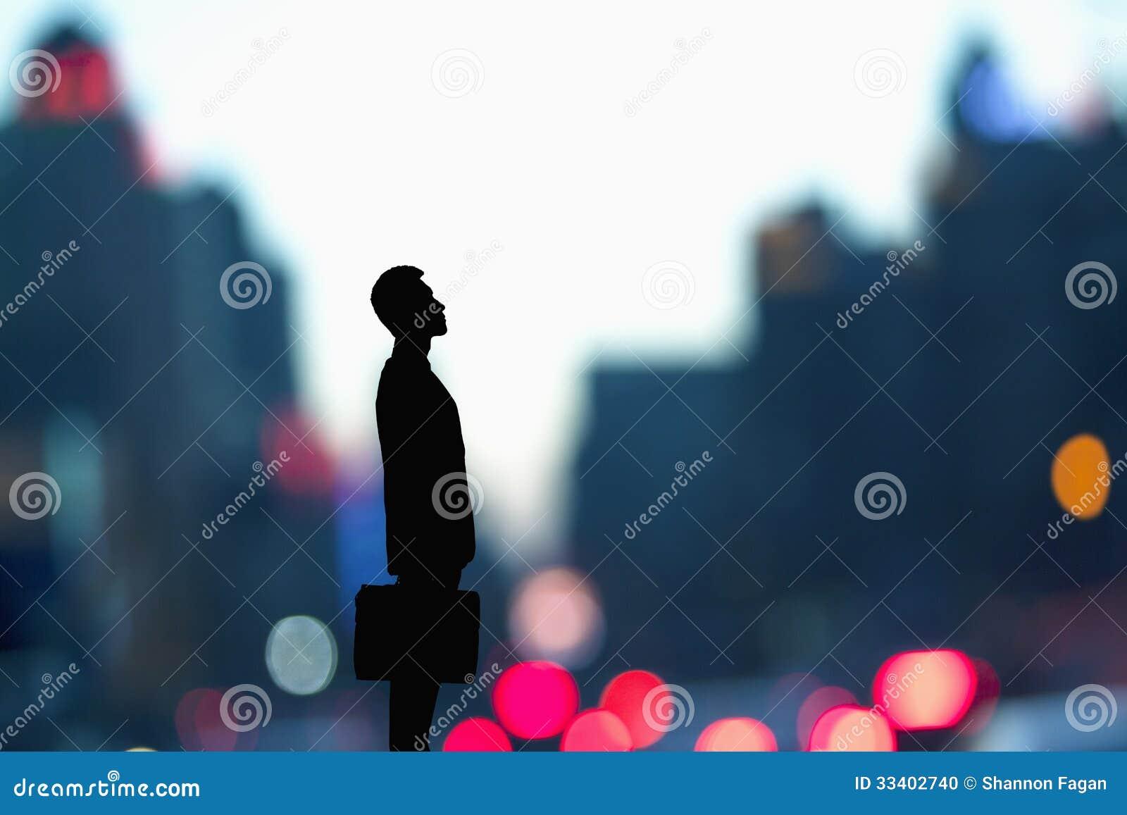 Konturn av affärsmannen som rymmer en portfölj med den suddiga staden, tänder bak honom