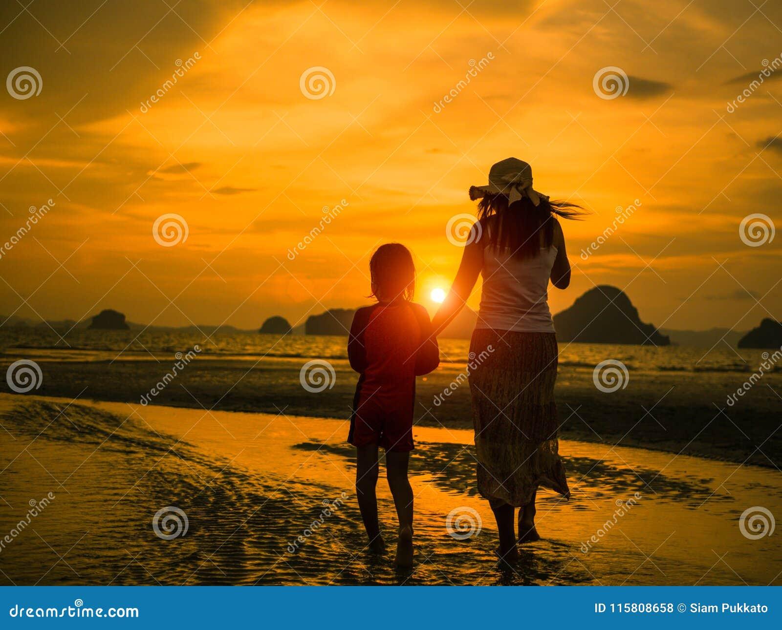 Konturn av handen för moderinnehavungen och går på stranden under solnedgång