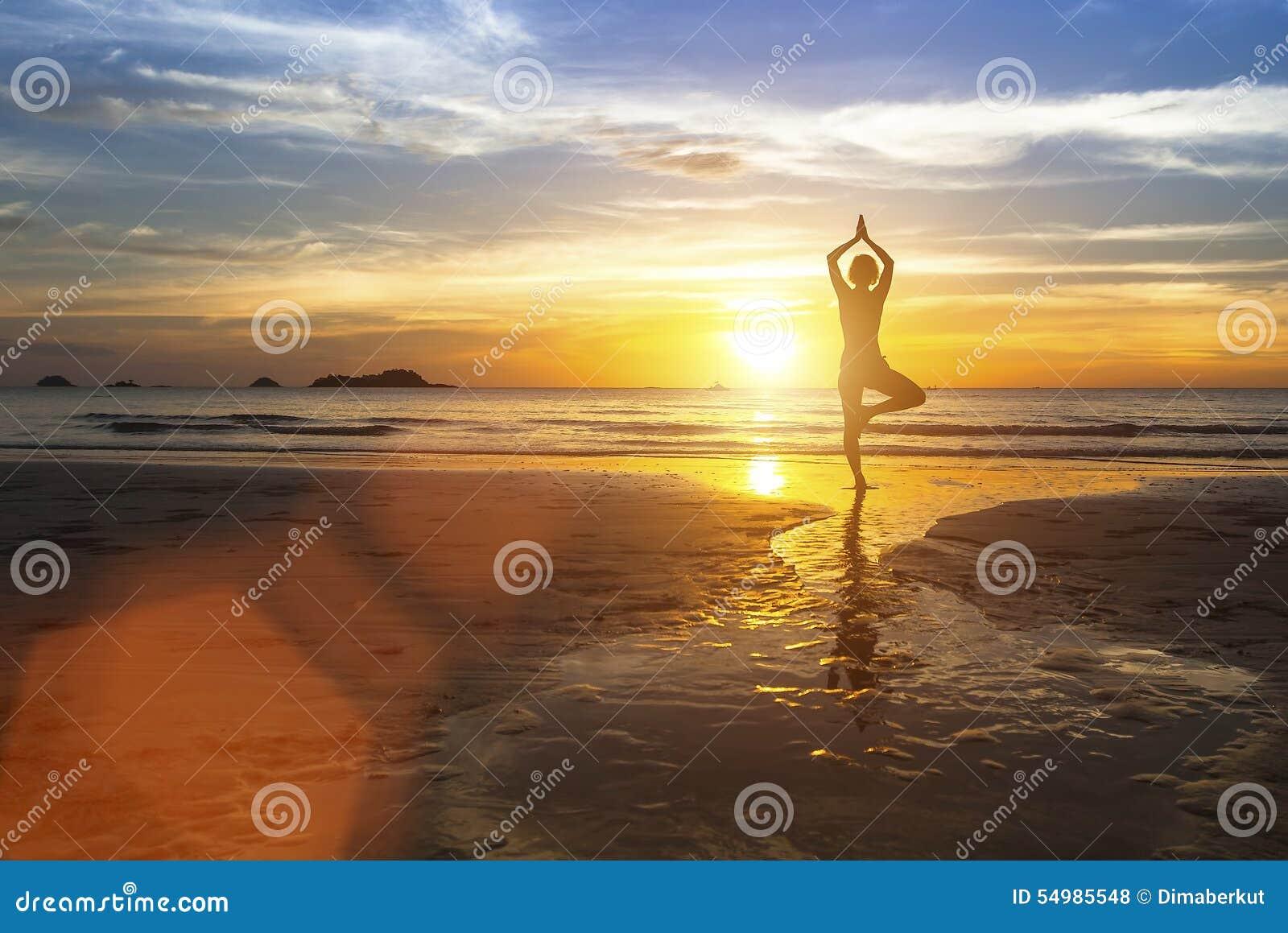 Konturn av kvinnaanseendet på yoga poserar på stranden