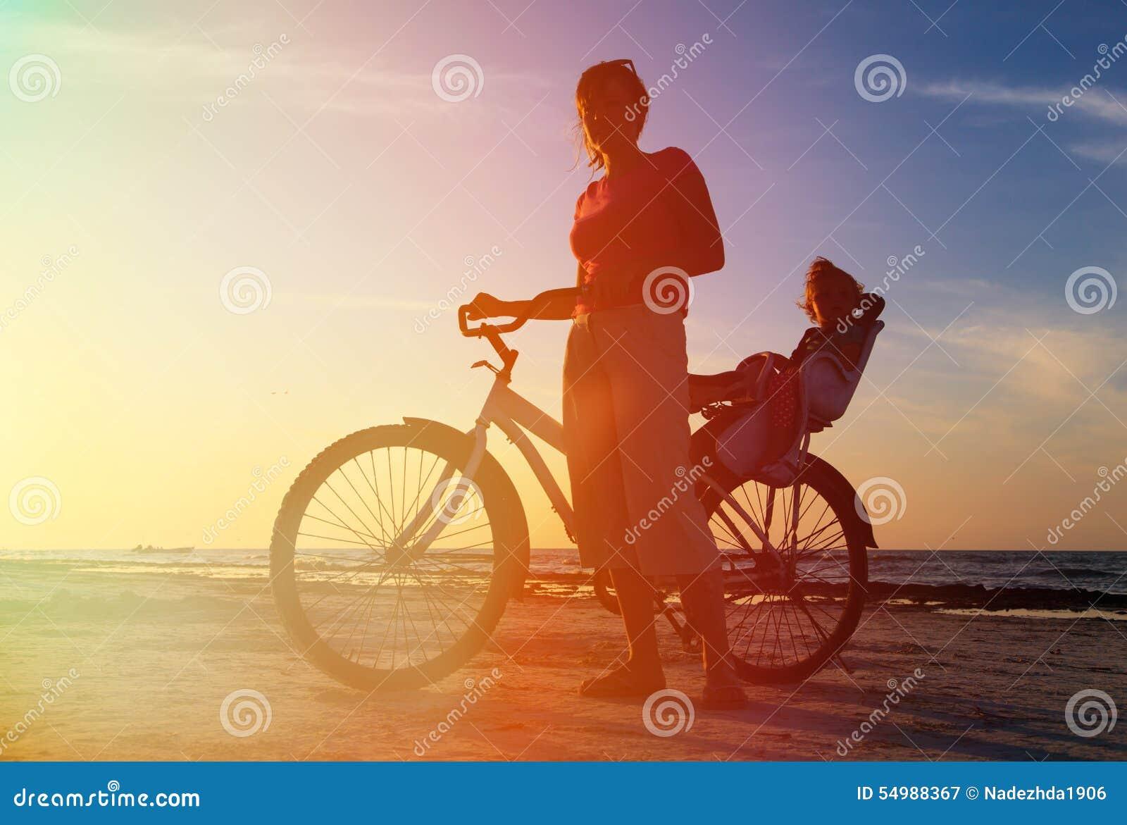 Konturn av modern och behandla som ett barn att cykla på solnedgången