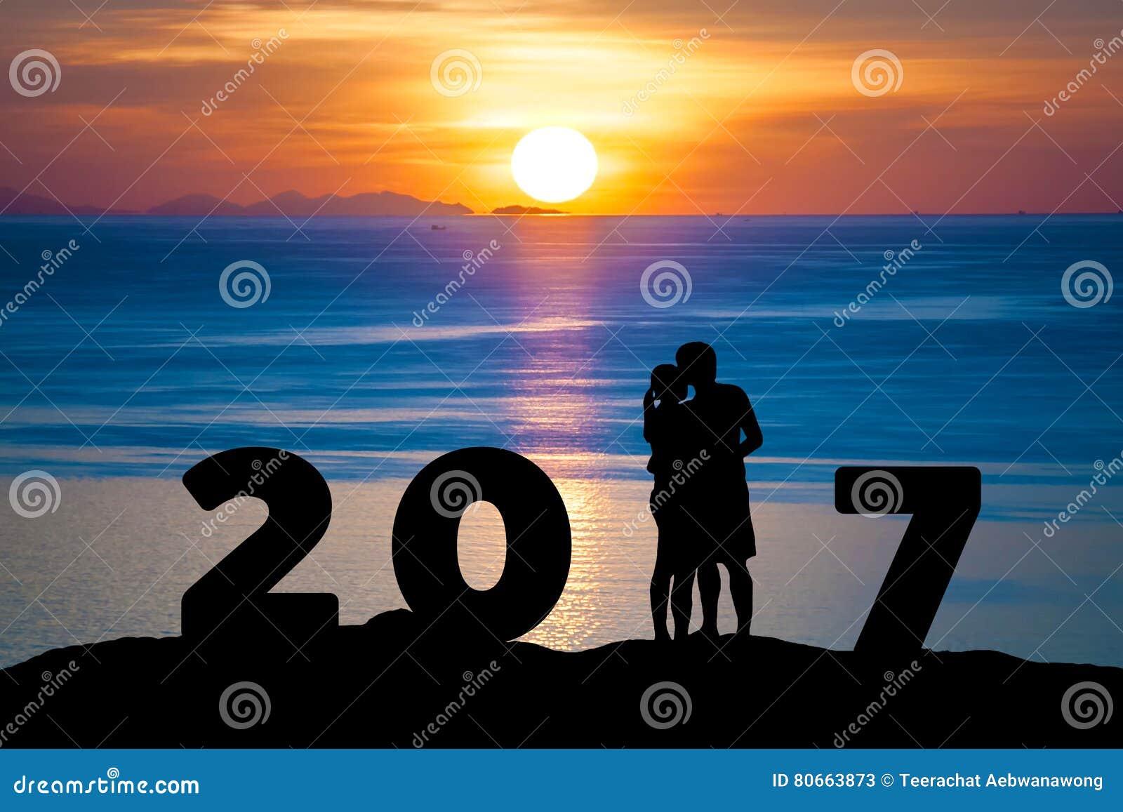 Konturn av romantiker ett par kramar att kyssa mot sommarhavet i solnedgångskymninghimmel, medan fira det lyckliga nya året 2017