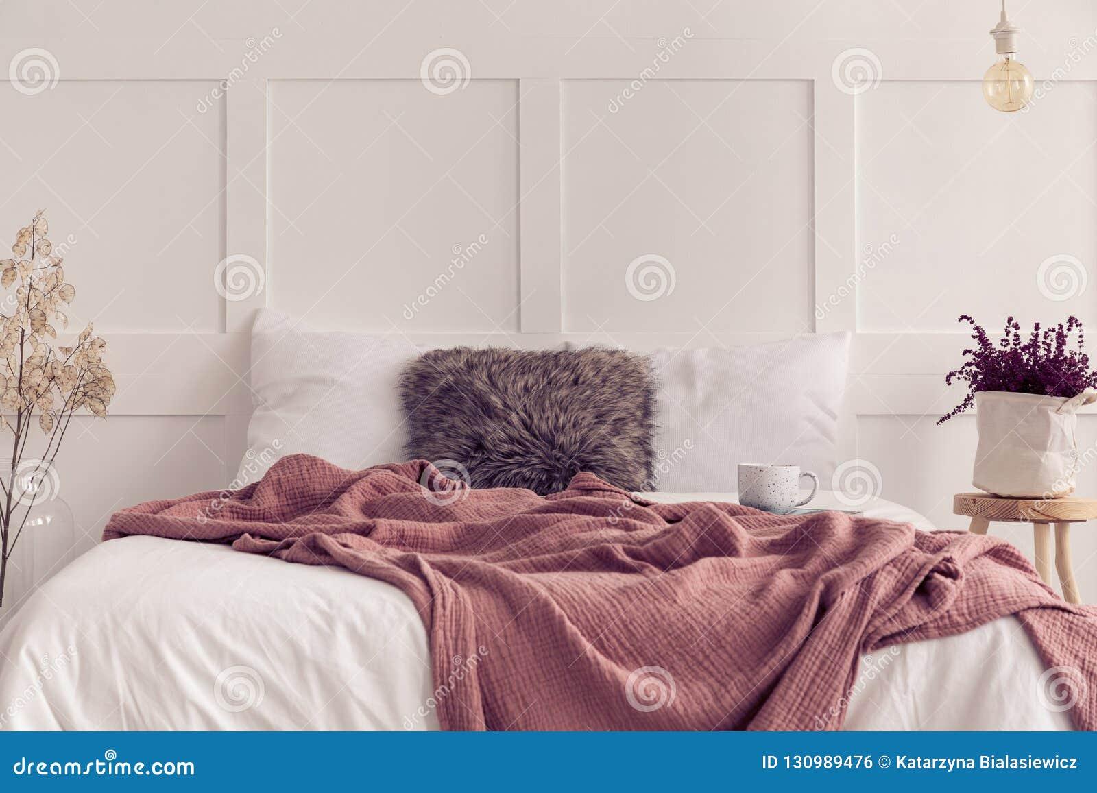 Konungformatsäng med vit sängkläder och smutsig rosa filt, verkligt foto med kopieringsutrymme