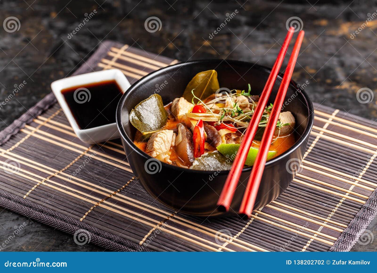 Konzept der asiatischen Küche Thailändische Suppe Tom-Jamswurzel der Hühnerbrühe und der Kokosmilch, der Pilze, des Huhns, der Pa