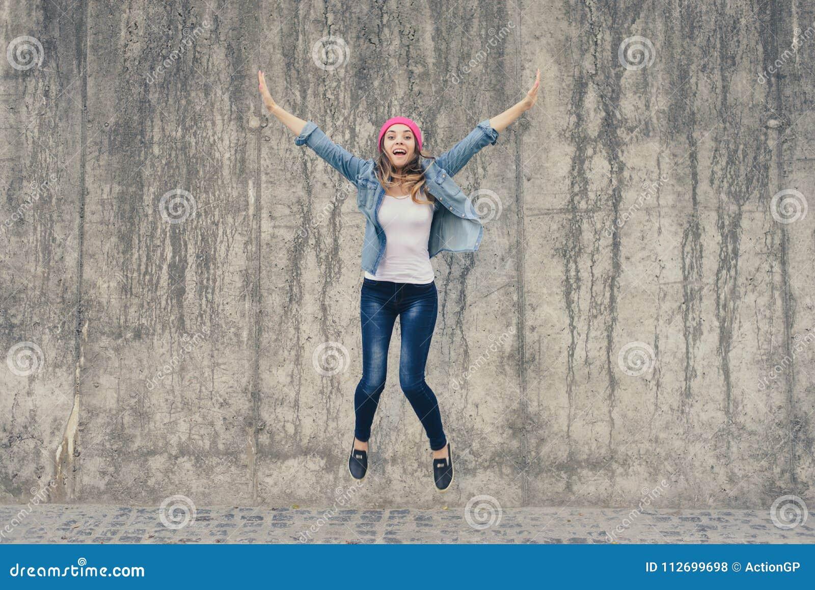 Konzept der Freude und der Freiheit, Leben ohne Probleme Verrücktes, extrem glückliches Mädchen in der Jeanskleidung und rosa Hut