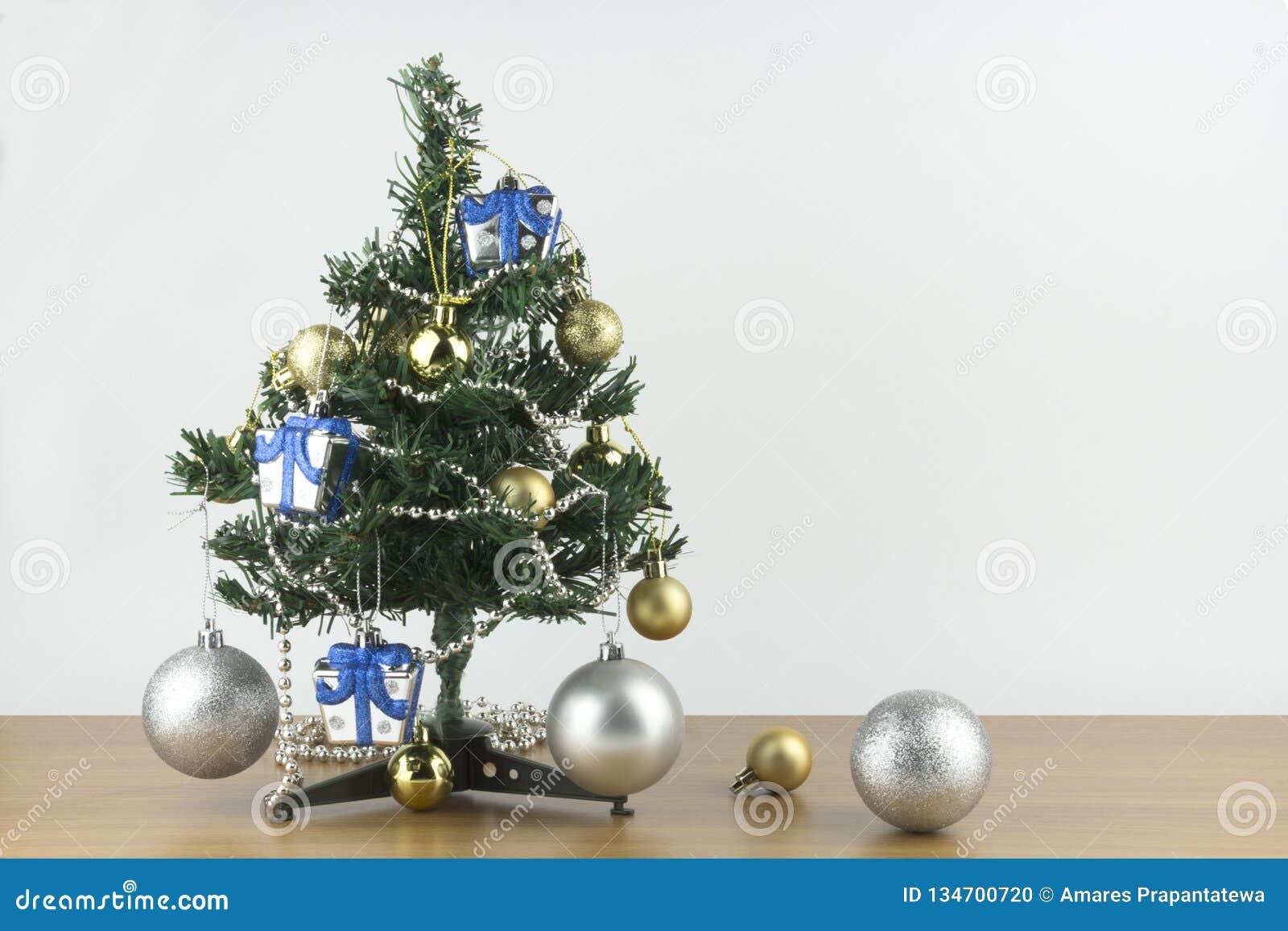 Konzept der frohen Weihnachten und des neuen Jahres, kleiner Weihnachtsbaum wird mit Verzierungen auf Holztisch- und weißemhinter