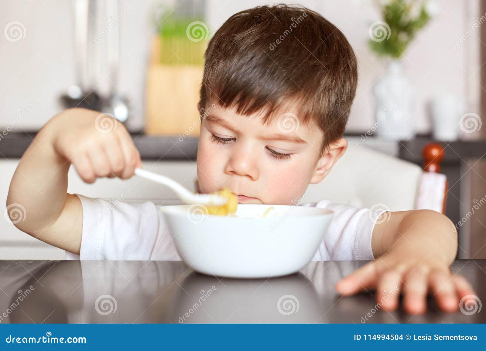 Konzept der gesunden Ernährung und der Kinder Hübsches kleines Kind isst mit dem köstlichen Brei des großen Appetits, der von der