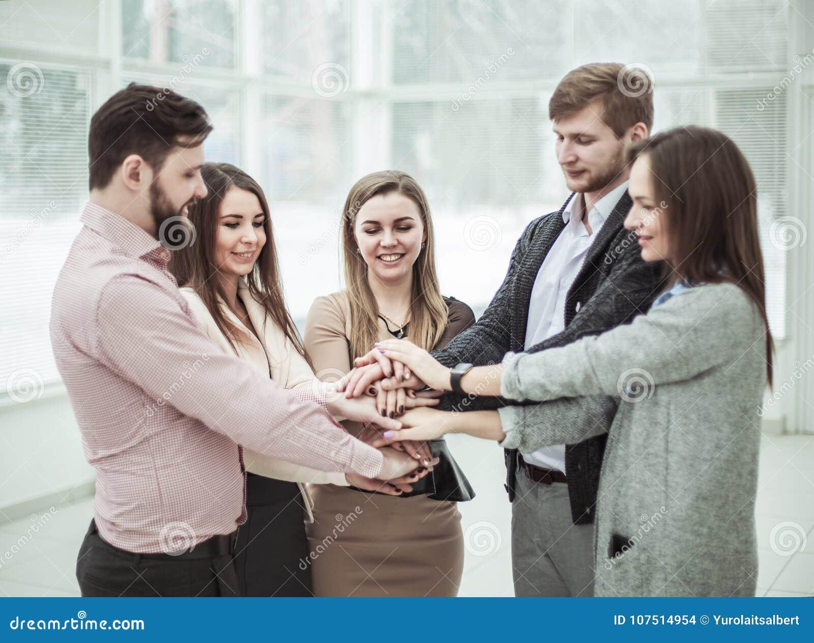 Konzept der Teamwork: freundliches Geschäftsteam, das in einem Kreis, Hände zusammen umklammert steht