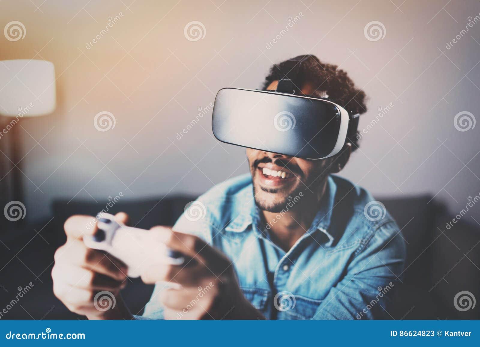 Konzept der Technologie, des Spiels, der Unterhaltung und der Leute Afrikanischer Mann, der Glasvideospiel der virtuellen Realitä