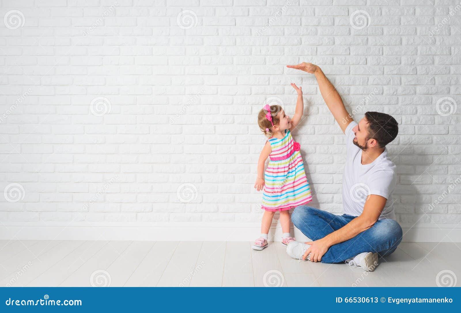 Konzept Vati misst Wachstum ihrer Kindertochter an einer Wand