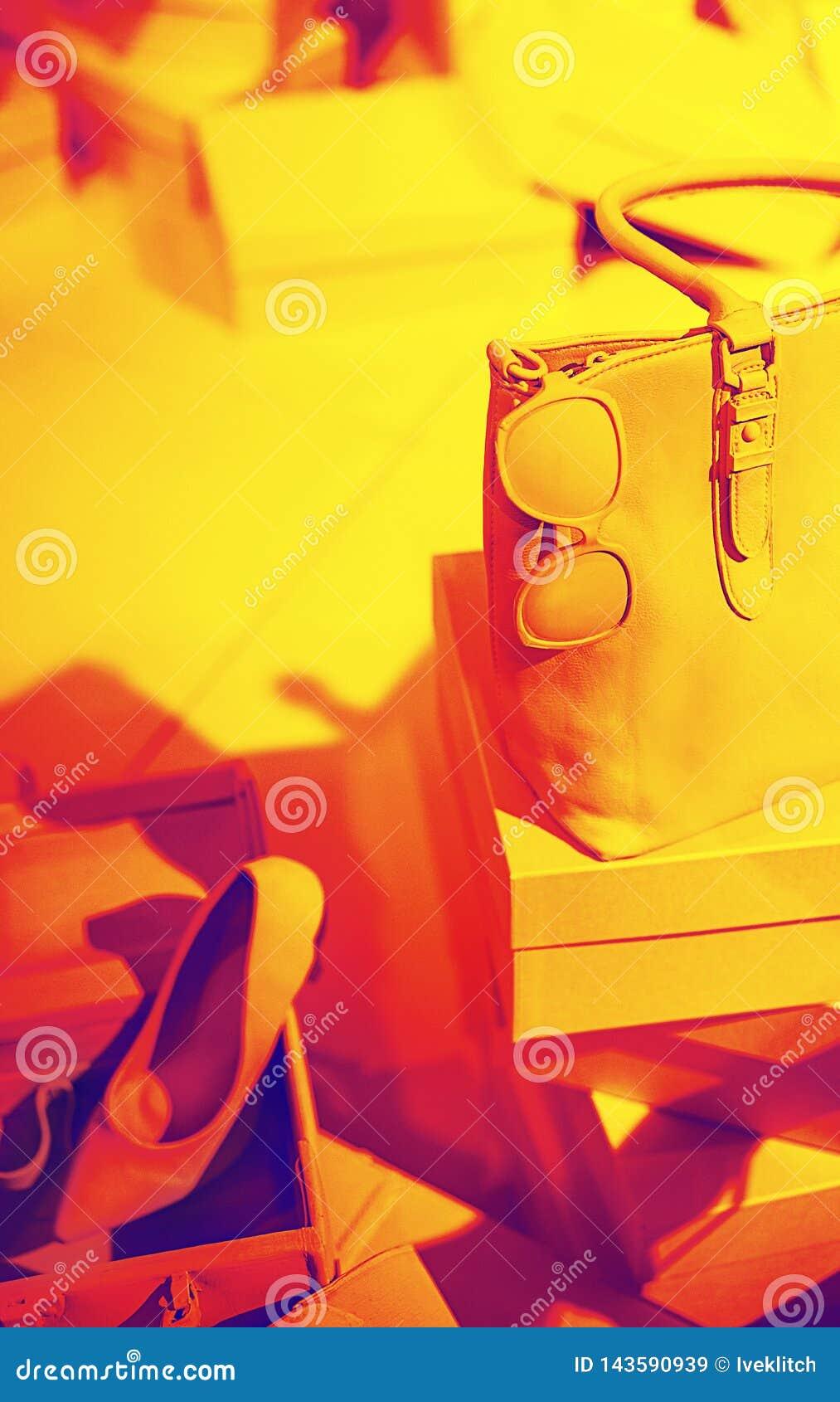 Konzept von modischen weiblichen Zusätzen bauschen sich, Sonnenbrille, Schuhe auf leeren Kästen und roter gelber Hintergrund