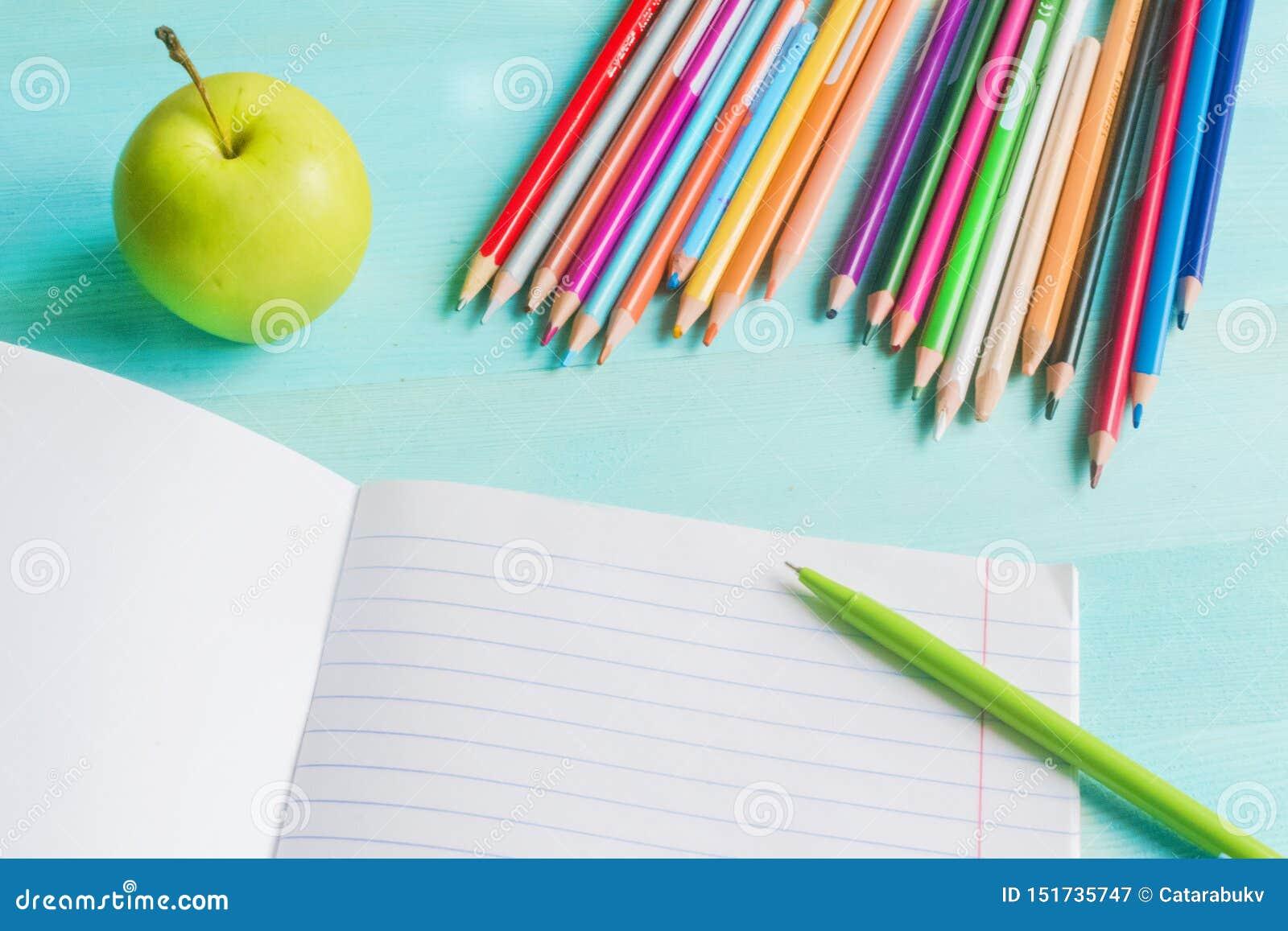 Konzept zur?ck zu Schule Schulzusätze, farbige Bleistifte, Stift mit leerem Notizbuch auf blauem hölzernem Hintergrund