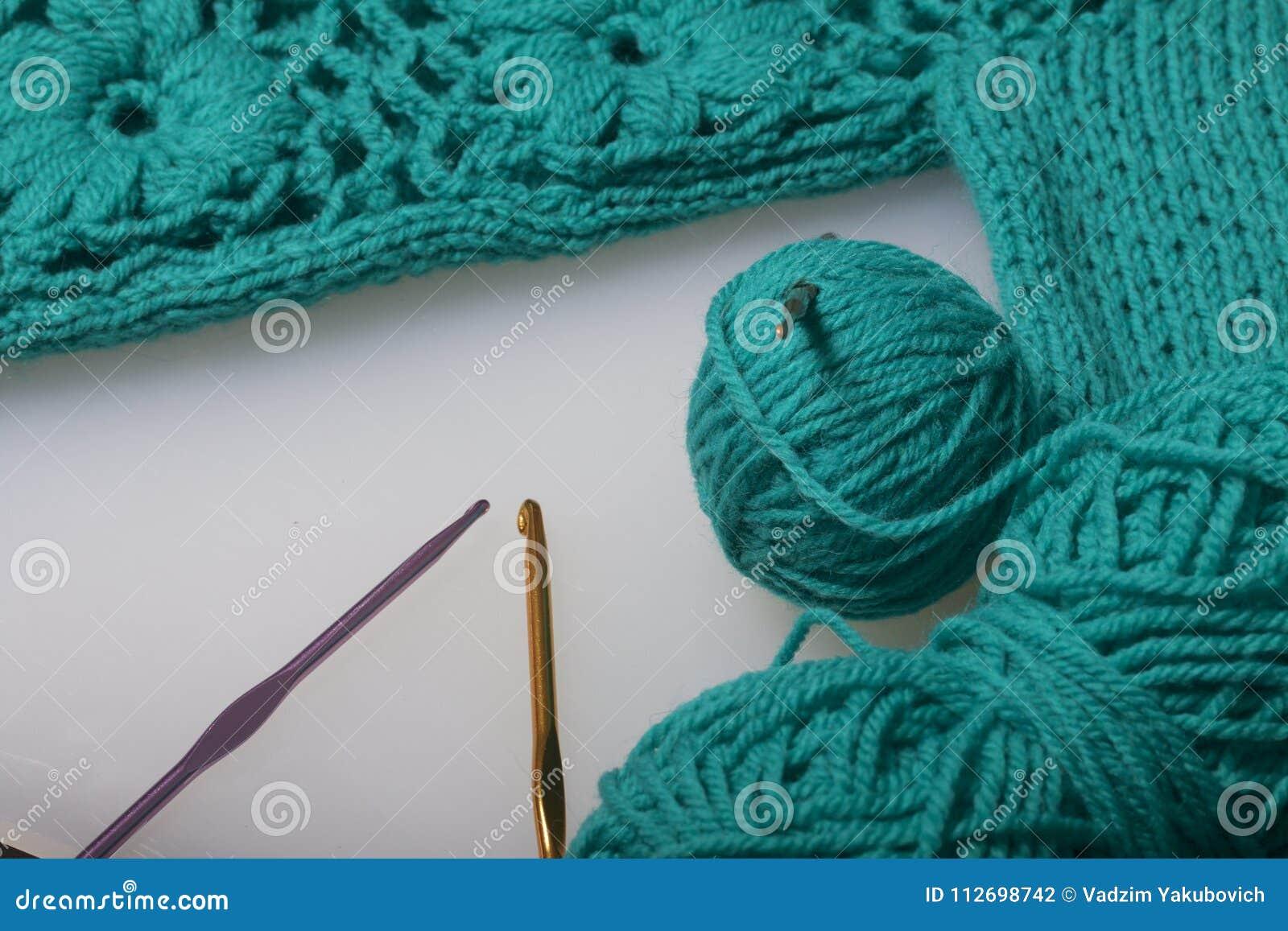 Koorden van draad voor het breien smaragdgroene kleur en haken voor het breien Lig op een klaar gebreid product
