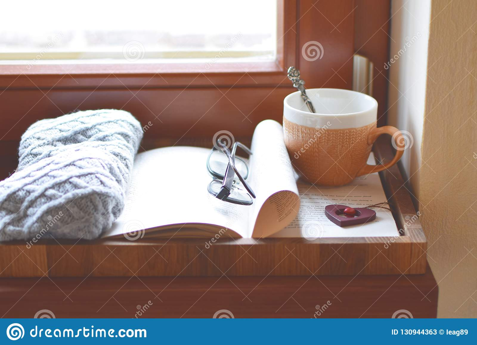 Kop thee, boek, de vensterbank van het glazenvenster